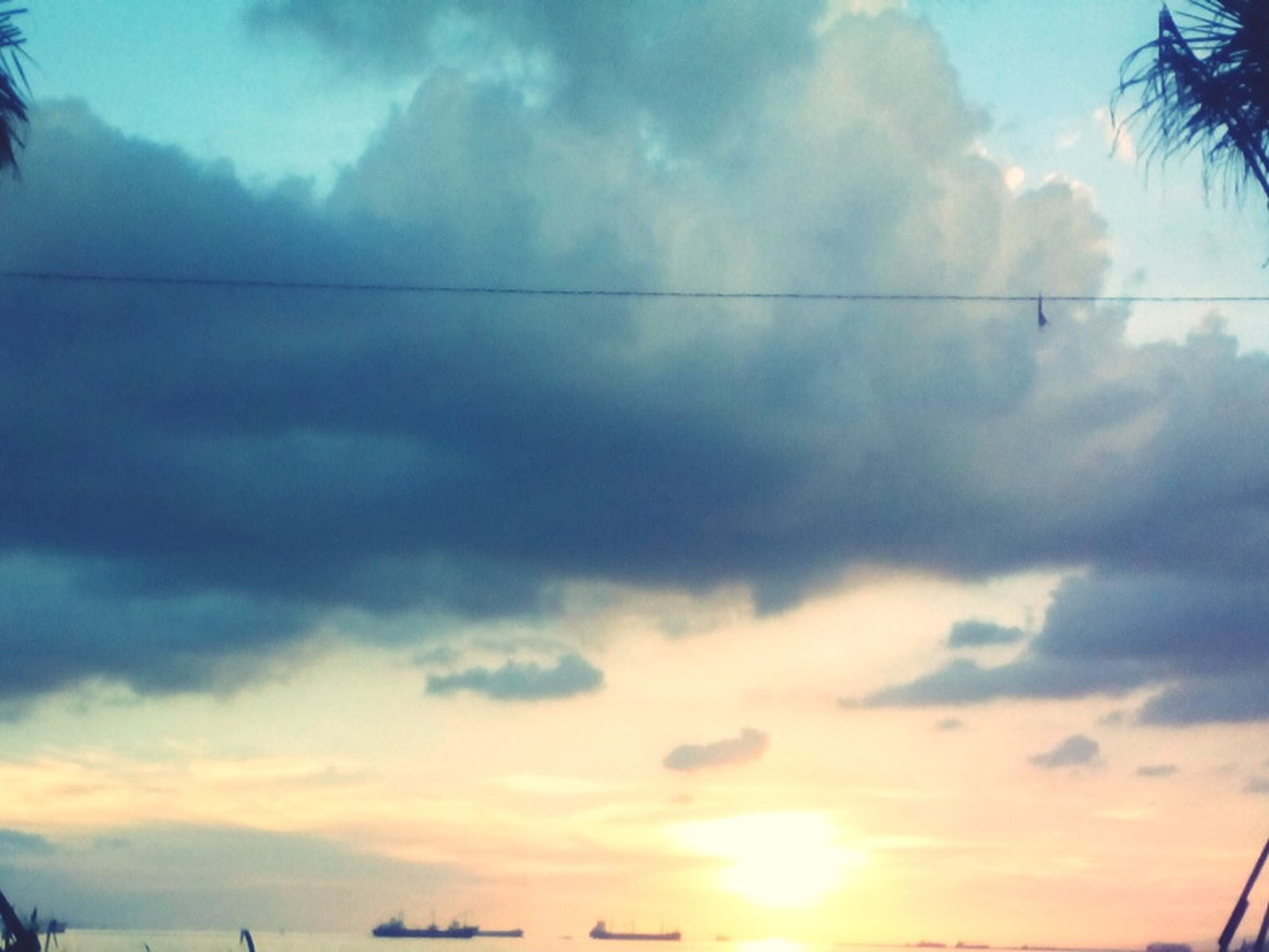 sky, cloud - sky, sunset, low angle view, cloudy, cloud, beauty in nature, silhouette, tranquility, scenics, nature, tranquil scene, sun, tree, sunlight, sunbeam, outdoors, power line, no people, idyllic