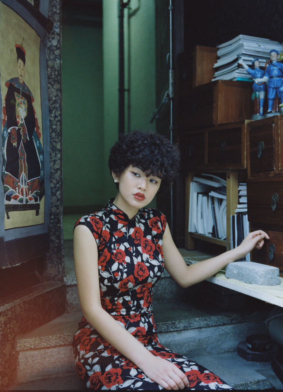 Cheongsam Childhood Curly Hair Day Elementary Age Girls Indoors  Leisure Activity Lifestyles Looking Down One Person People Portrait Radiator Real People Sitting Three Quarter Length Young Adult