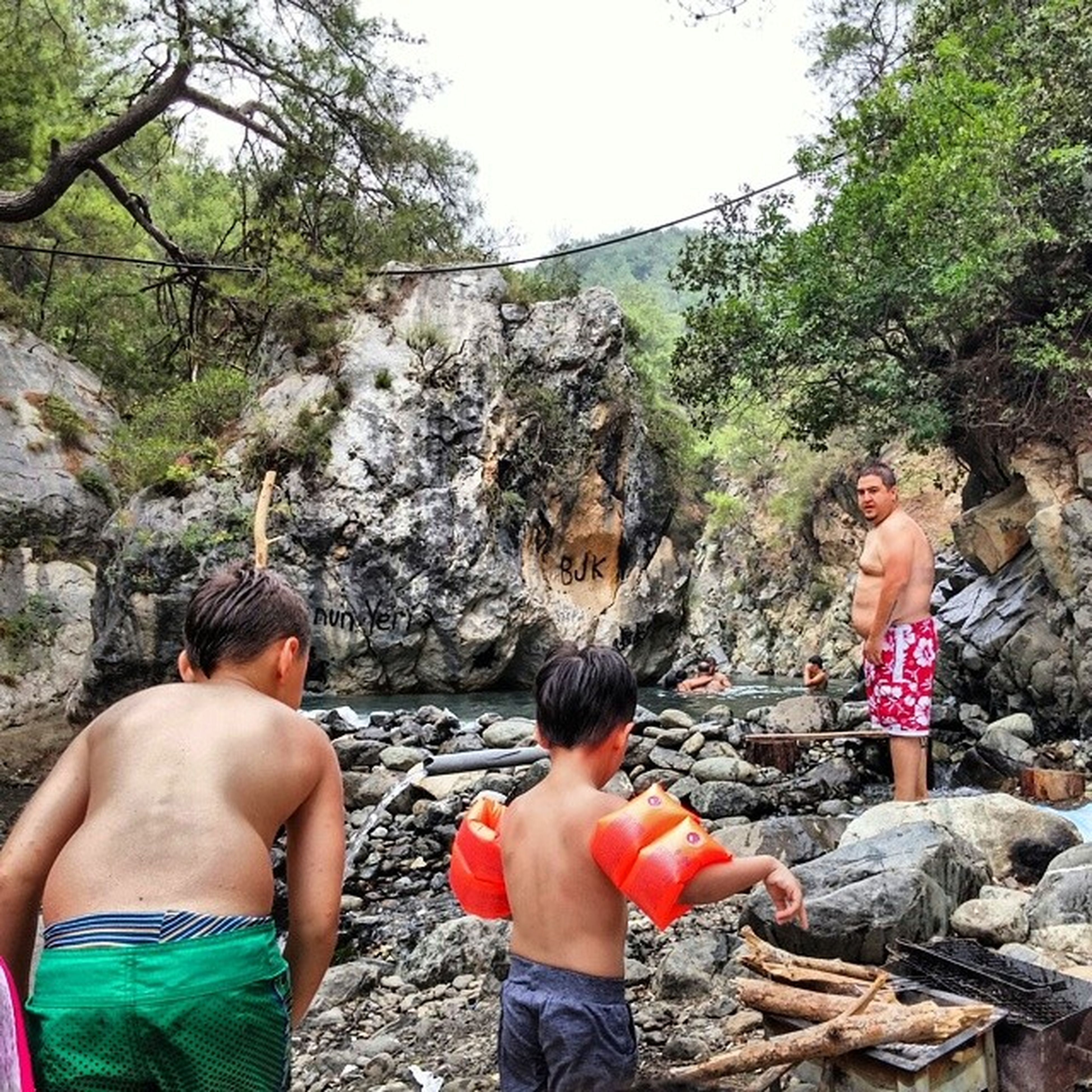 lifestyles, leisure activity, person, casual clothing, rock - object, togetherness, childhood, tree, bonding, love, standing, vacations, full length, elementary age, young adult, boys, three quarter length