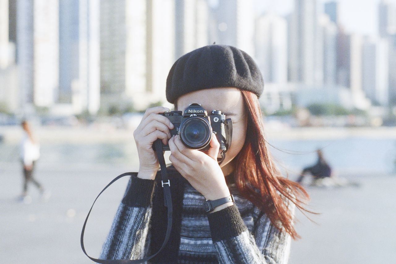 camera - photographic equipment, photography themes, photographing, digital camera, technology, photographer, real people, leisure activity, focus on foreground, camera, digital single-lens reflex camera, one person, holding, slr camera, day, lifestyles, outdoors, architecture, portrait, city, close-up, people