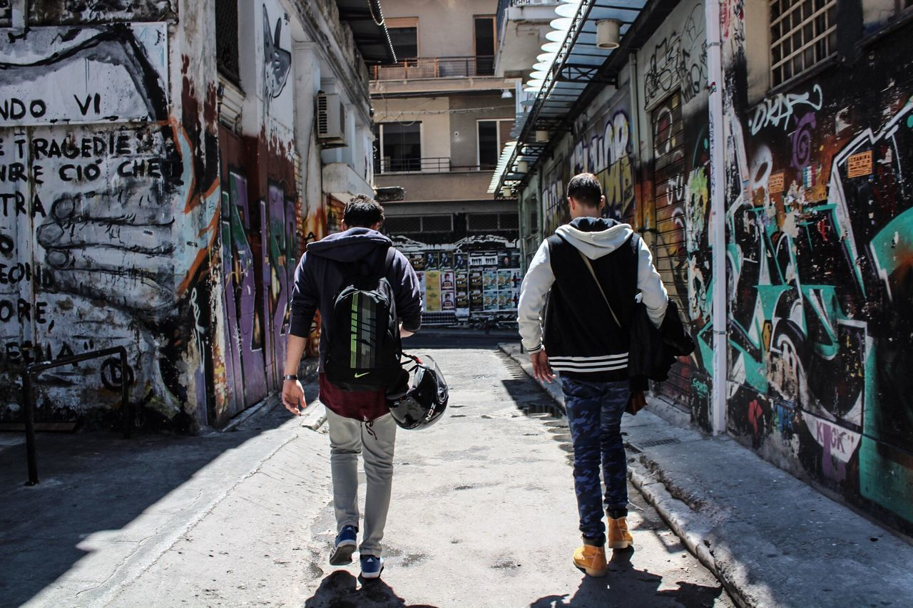 full length, walking, real people, architecture, two people, rear view, graffiti, built structure, building exterior, men, leisure activity, day, casual clothing, backpack, women, the way forward, togetherness, lifestyles, standing, outdoors, city, adult, people
