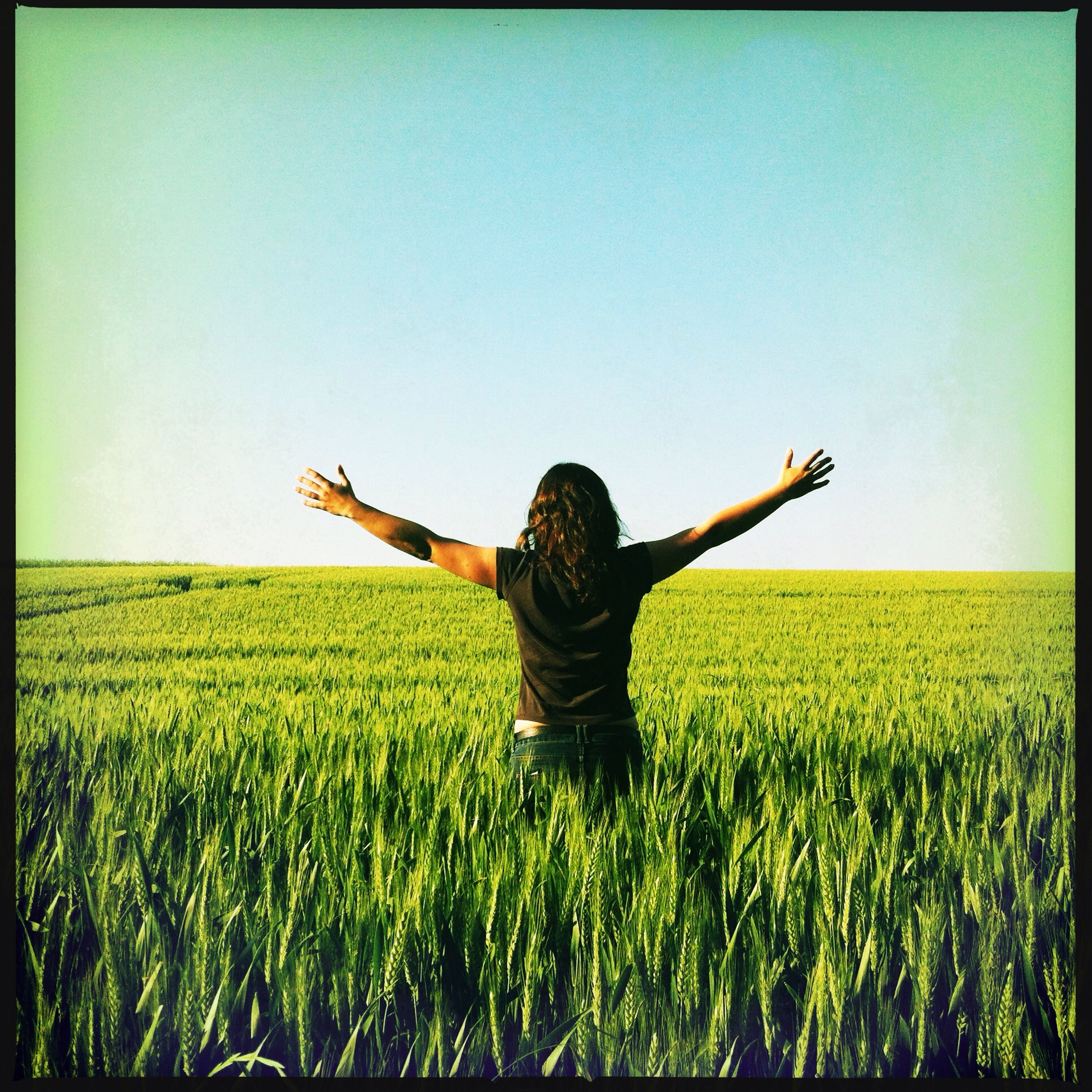 lifestyles, field, leisure activity, standing, grass, casual clothing, full length, transfer print, clear sky, copy space, landscape, three quarter length, auto post production filter, young adult, arms outstretched, sky, person, grassy