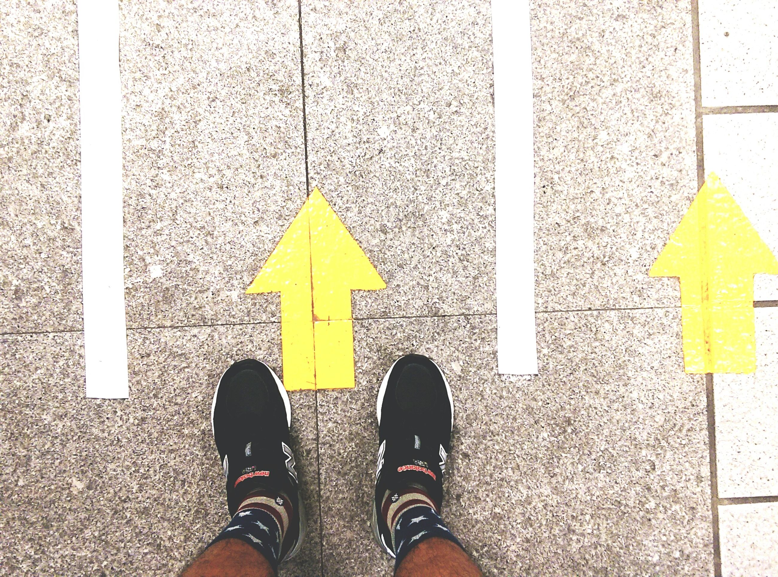 low section, personal perspective, person, standing, shoe, guidance, road marking, street, communication, arrow symbol, sign, lifestyles, yellow, human foot, direction, men, text