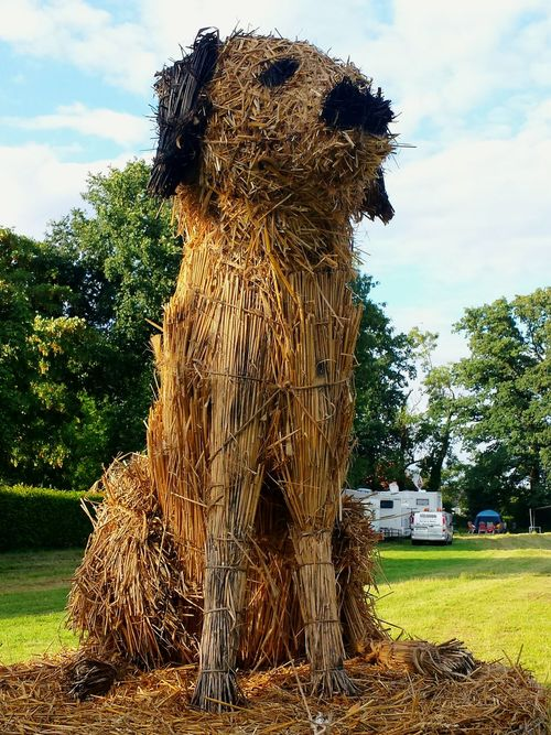 Home Is Where The Art Is Artificial Dog Artistic Expression Cute Art Art Installation Arts And Crafts Arts Culture And Entertainment Art, Drawing, Creativity Straw Dog onStraw Bale Energy Tower Against Blue Sky Art Is Everywhere