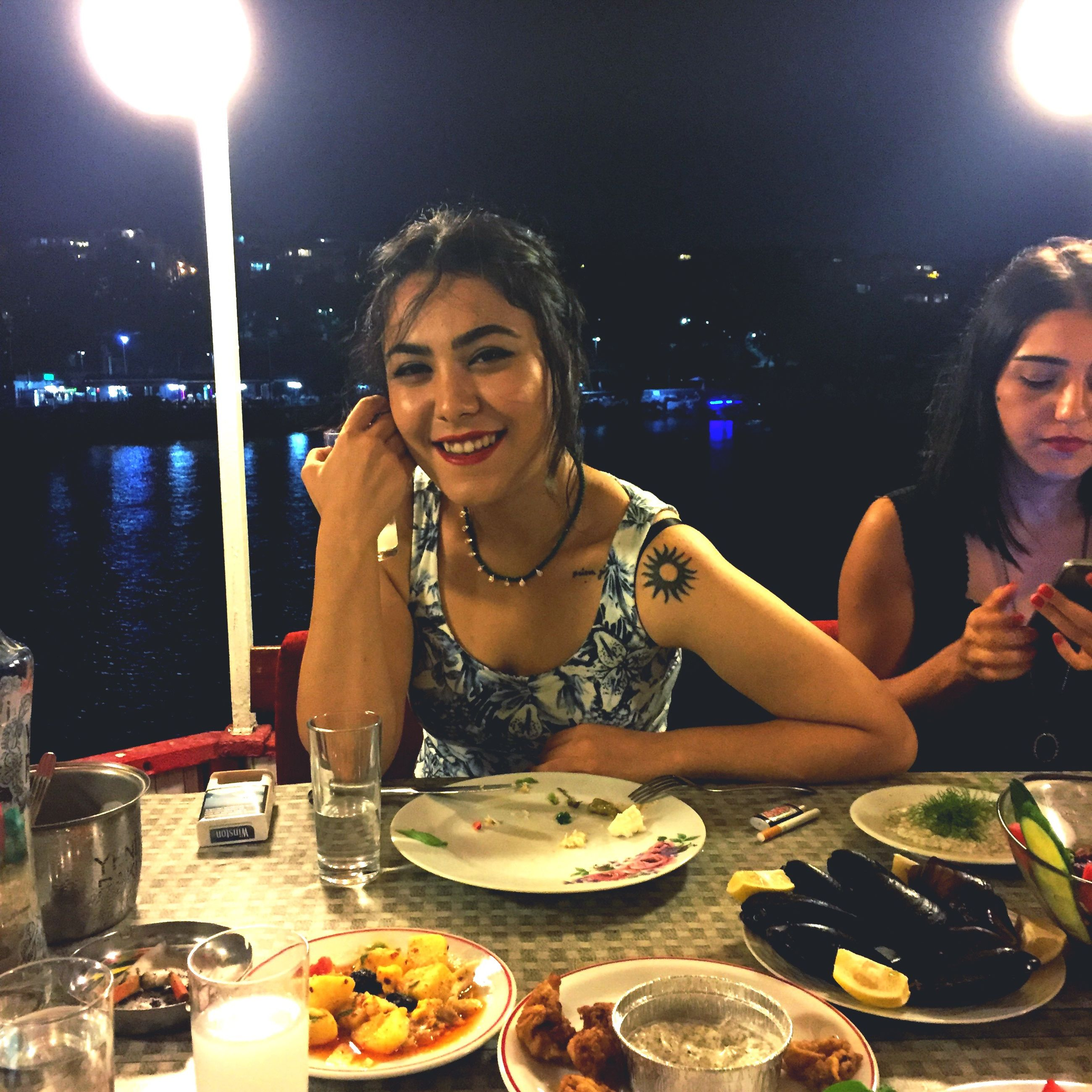 illuminated, food and drink, night, togetherness, birthday cake, headshot, celebration, lifestyles, food, birthday, leisure activity, eating, front view, in front of, young women, freshness, plate, enjoyment, water, dinner, ready-to-eat, indulgence, young adult, person, dessert