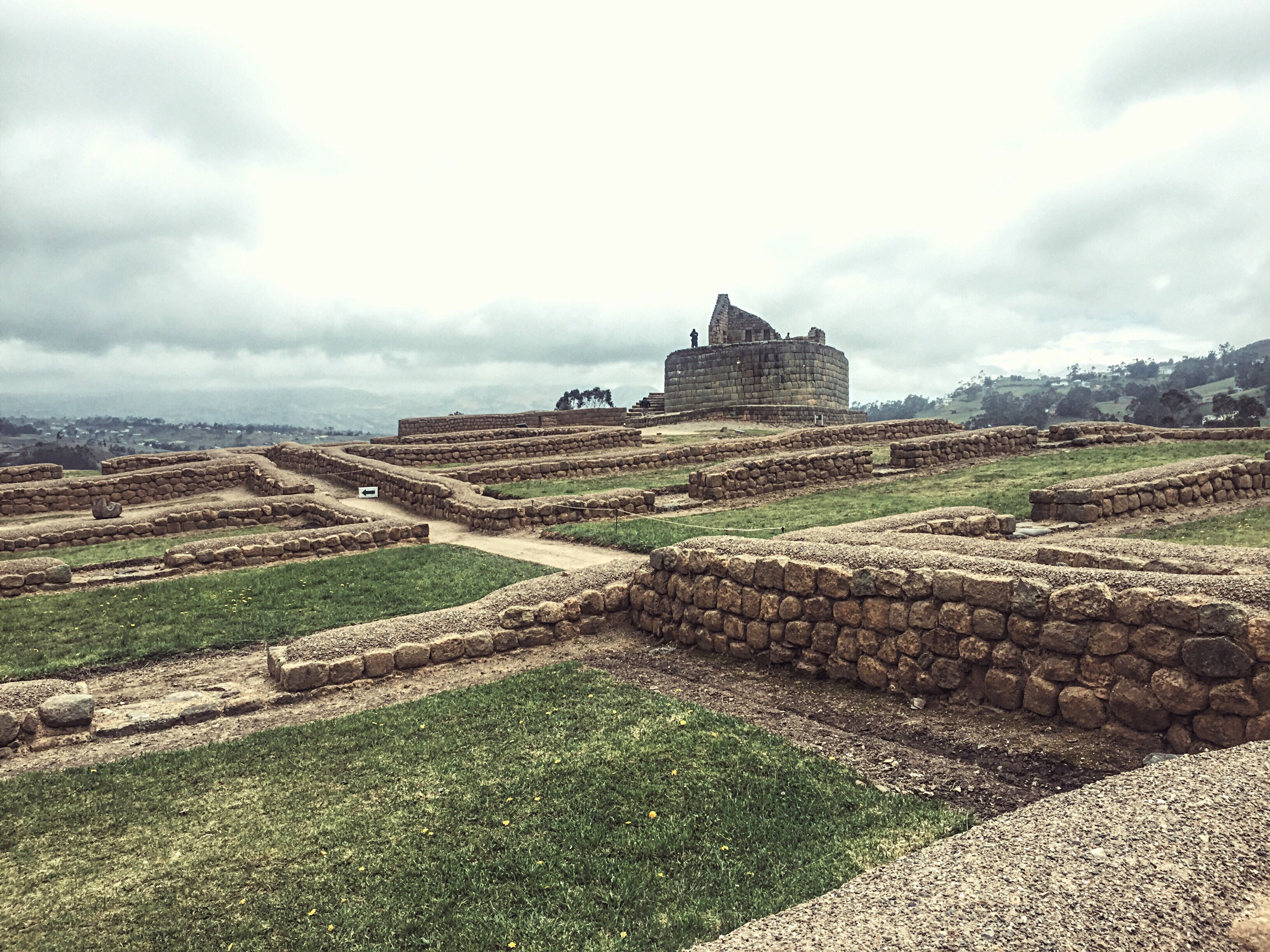sky, architecture, built structure, history, cloud - sky, landscape, old ruin, ancient, the past, tranquility, cloud, cloudy, tranquil scene, travel destinations, grass, nature, scenics, castle, day, tourism, hill, outdoors, no people, beauty in nature, rural scene, non-urban scene