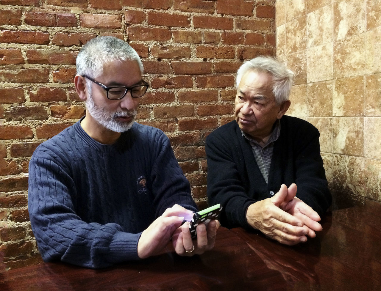 Father and Son Brick Wall Casual Clothing Concentration Conversation Day Father And Daughter Front View Leisure Activity Lifestyles Man With Cellphone Mature Adult Men In Corner Of Room Old And Young White Hair Men People Together By August 3 2016 People And Places