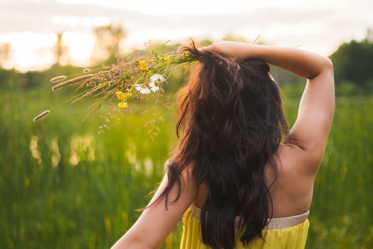 field, flower, focus on foreground, nature, real people, one person, growth, outdoors, long hair, plant, day, headshot, lifestyles, close-up, young adult