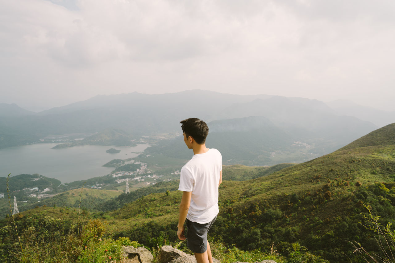 mountain, real people, nature, mountain range, rear view, beauty in nature, scenics, sky, standing, leisure activity, tranquility, casual clothing, one person, tranquil scene, landscape, lifestyles, outdoors, day, cloud - sky, grass, men, tree