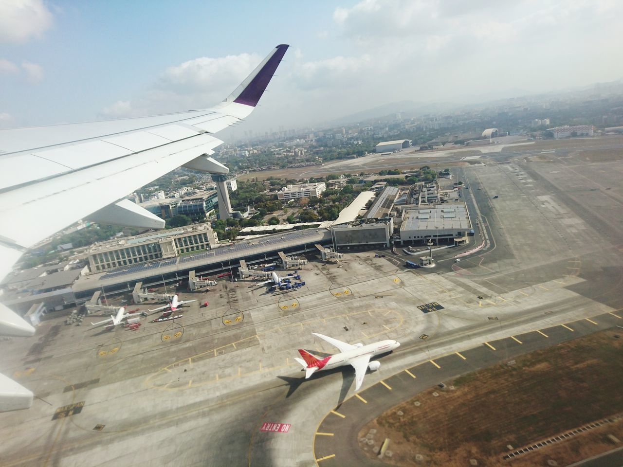 airplane, transportation, air vehicle, airport, mode of transport, aircraft wing, airport runway, flying, journey, day, aerial view, commercial airplane, cloud - sky, sky, travel, outdoors, land vehicle, no people, architecture, built structure, runway, city, airplane wing, aerospace industry