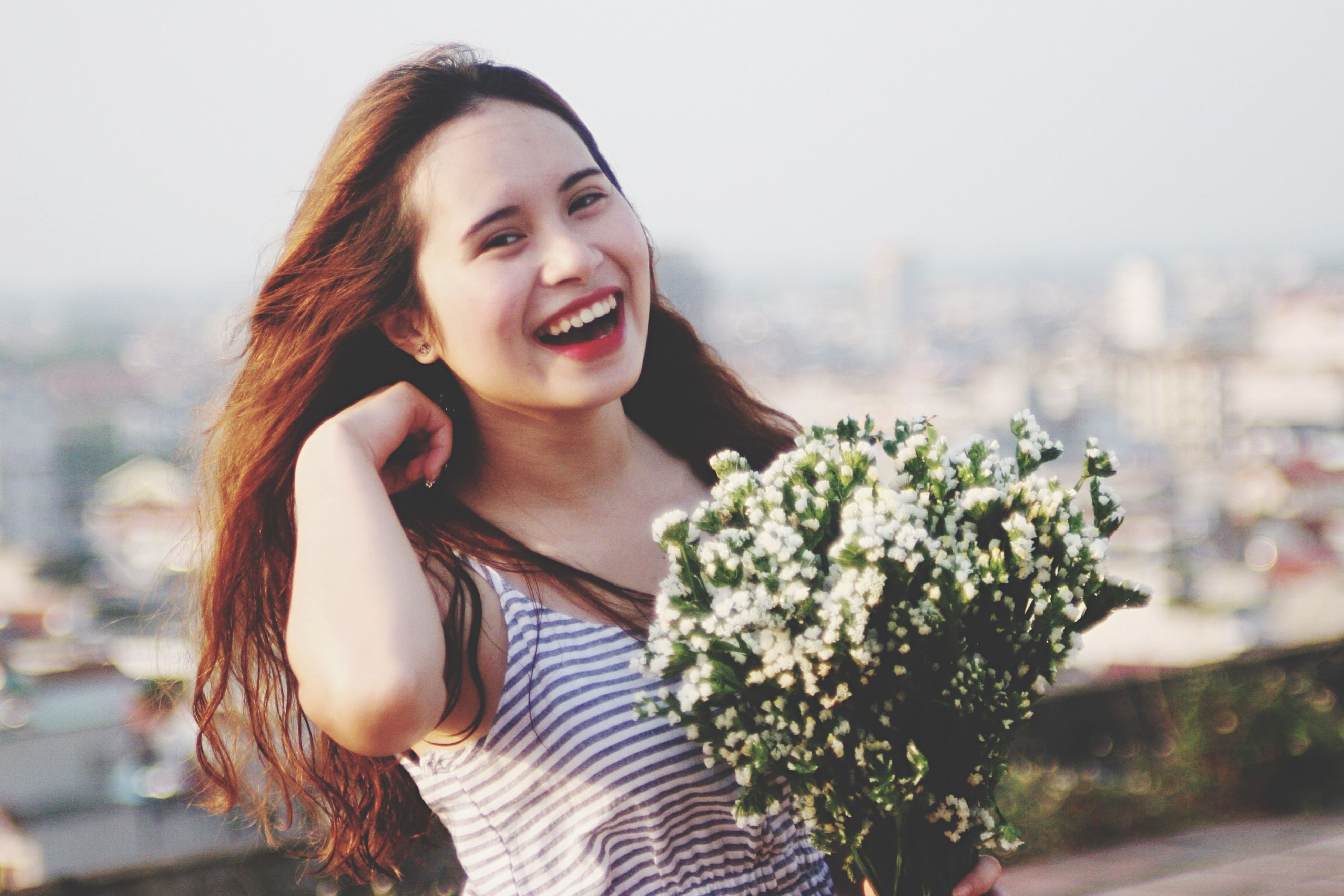 young adult, young women, person, lifestyles, focus on foreground, long hair, leisure activity, portrait, looking at camera, casual clothing, smiling, front view, waist up, standing, flower, three quarter length