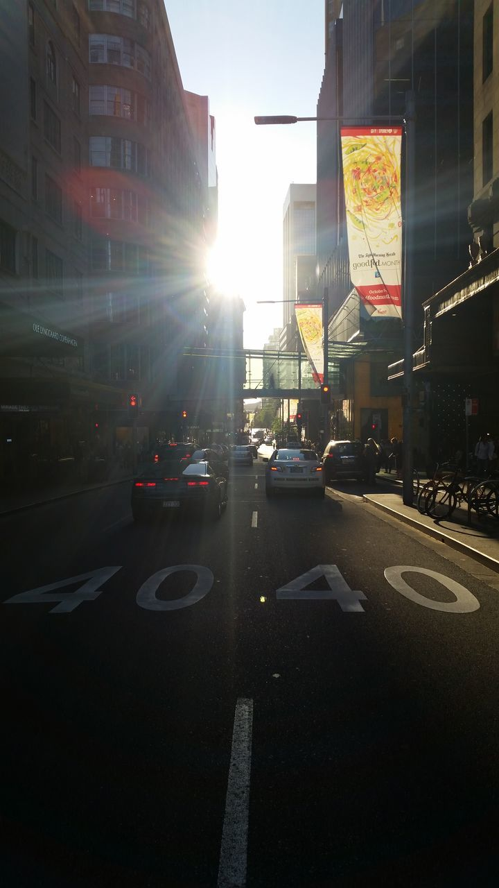 car, city, street, architecture, building exterior, transportation, land vehicle, lens flare, traffic, road, city street, built structure, outdoors, city life, no people, sunset, day, sky
