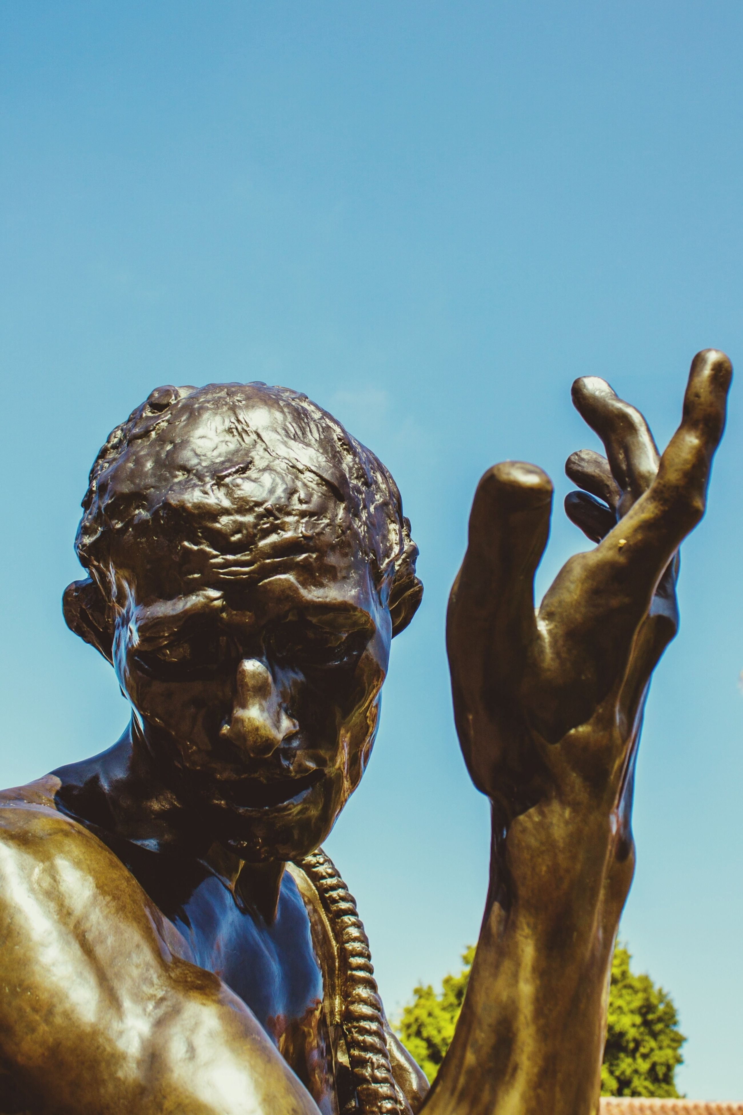 sculpture, statue, human representation, art and craft, art, low angle view, clear sky, creativity, blue, animal representation, copy space, carving - craft product, craft, sky, day, outdoors, no people, sunlight