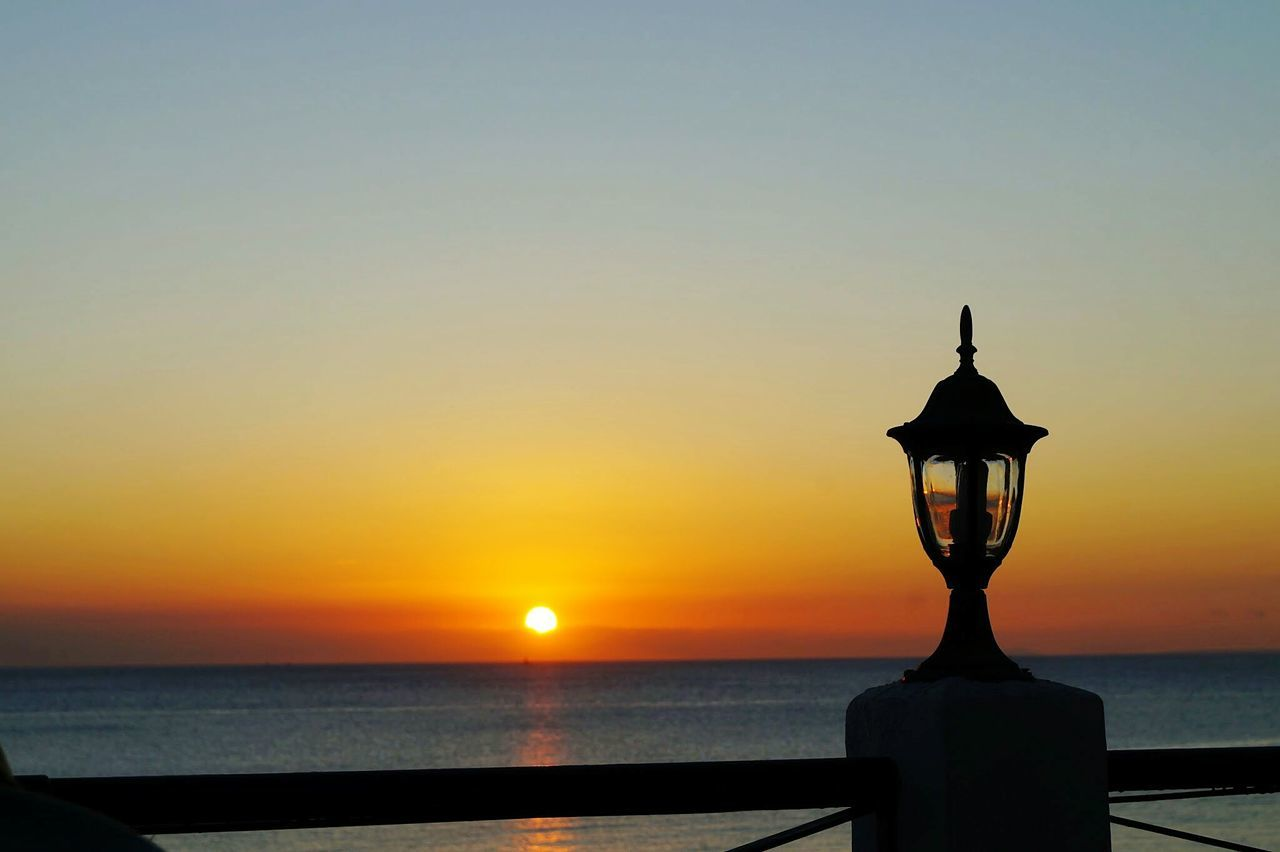 sunset, sea, sun, silhouette, sky, orange color, water, horizon over water, beauty in nature, tranquility, scenics, tranquil scene, nature, sunlight, outdoors, clear sky, no people, statue, close-up, day