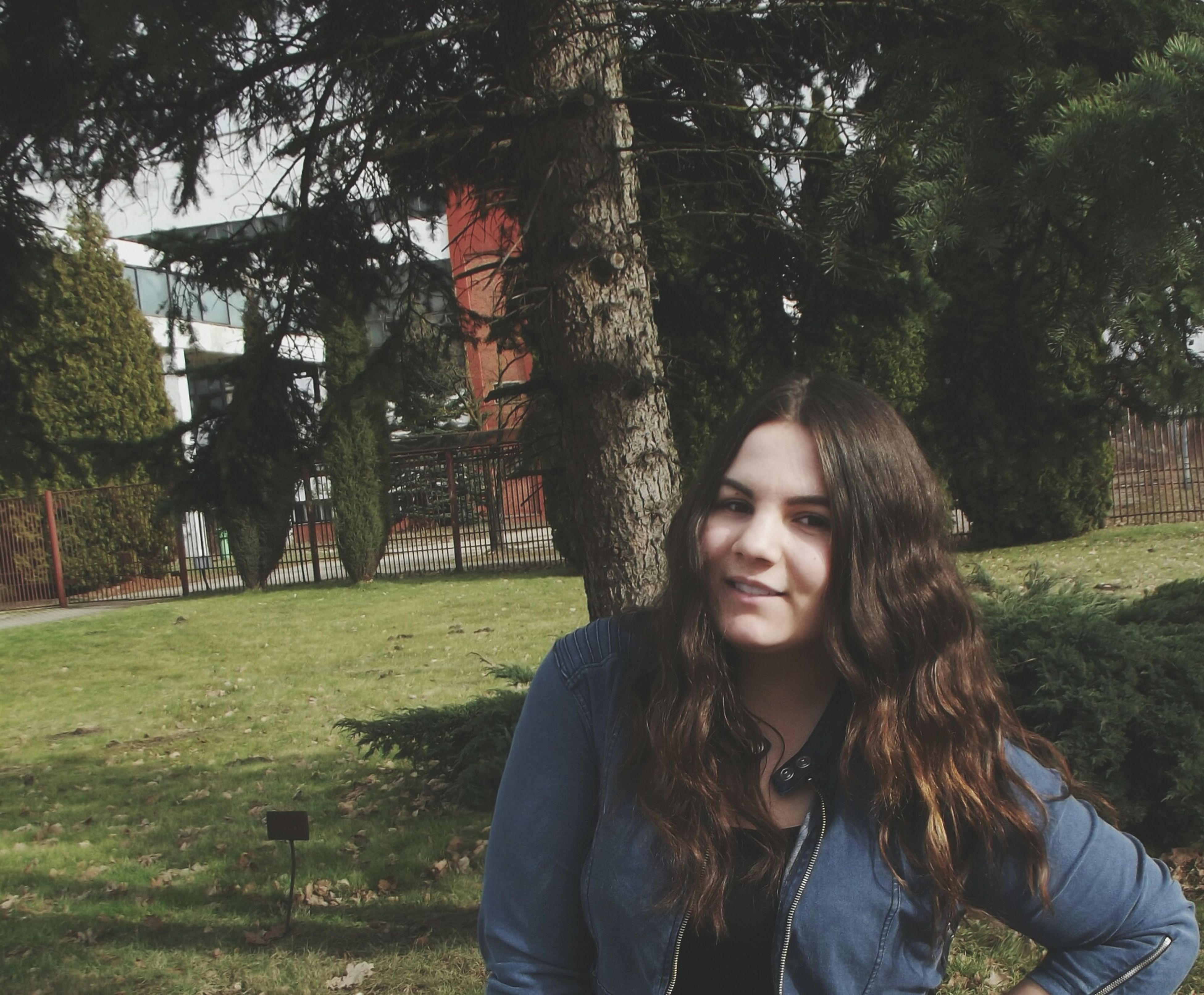 tree, young adult, lifestyles, leisure activity, person, young women, park - man made space, casual clothing, grass, looking at camera, portrait, smiling, front view, sunlight, long hair, park, day, outdoors