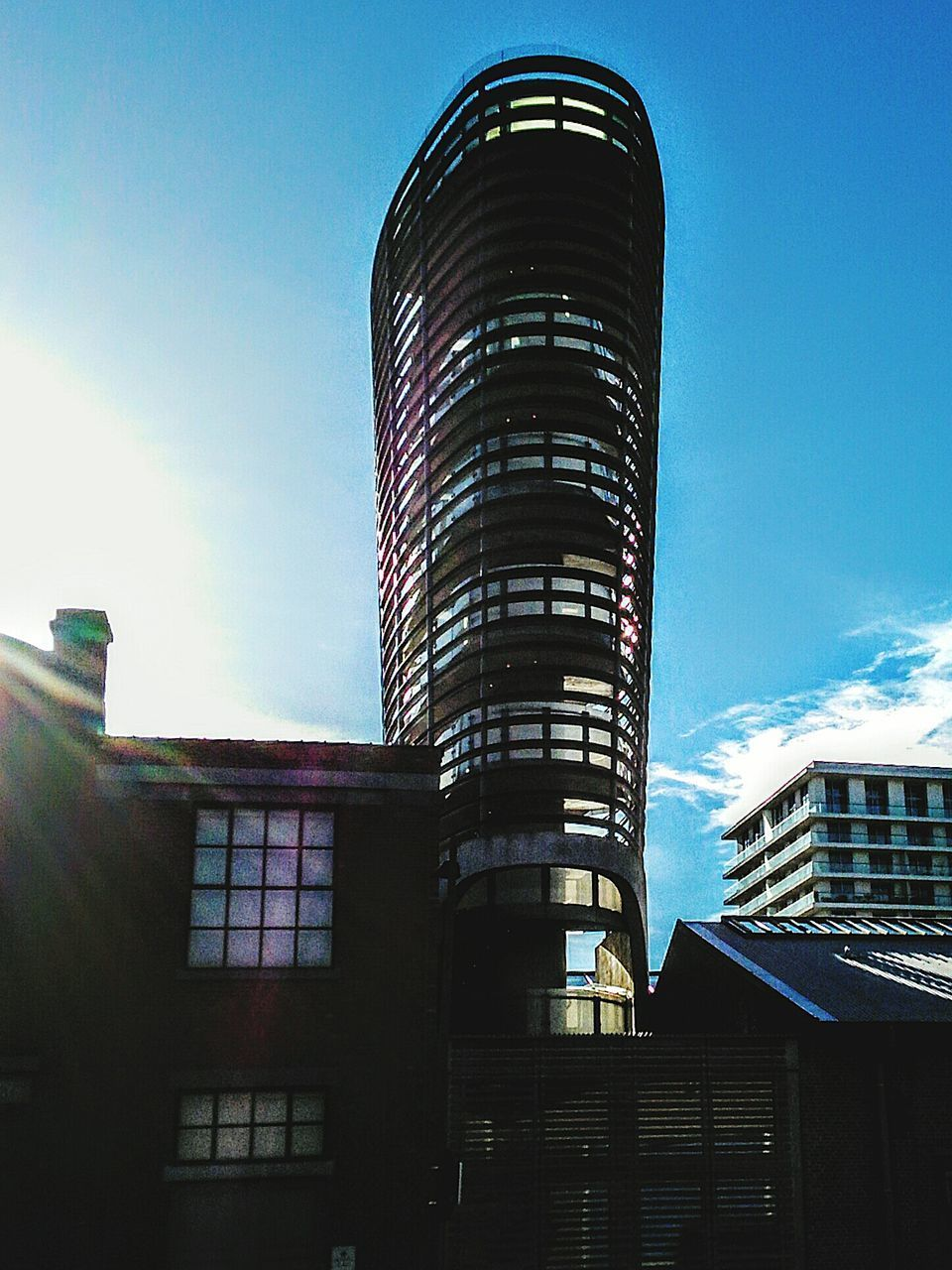 architecture, building exterior, built structure, low angle view, sky, sunlight, day, window, skyscraper, modern, no people, outdoors, city
