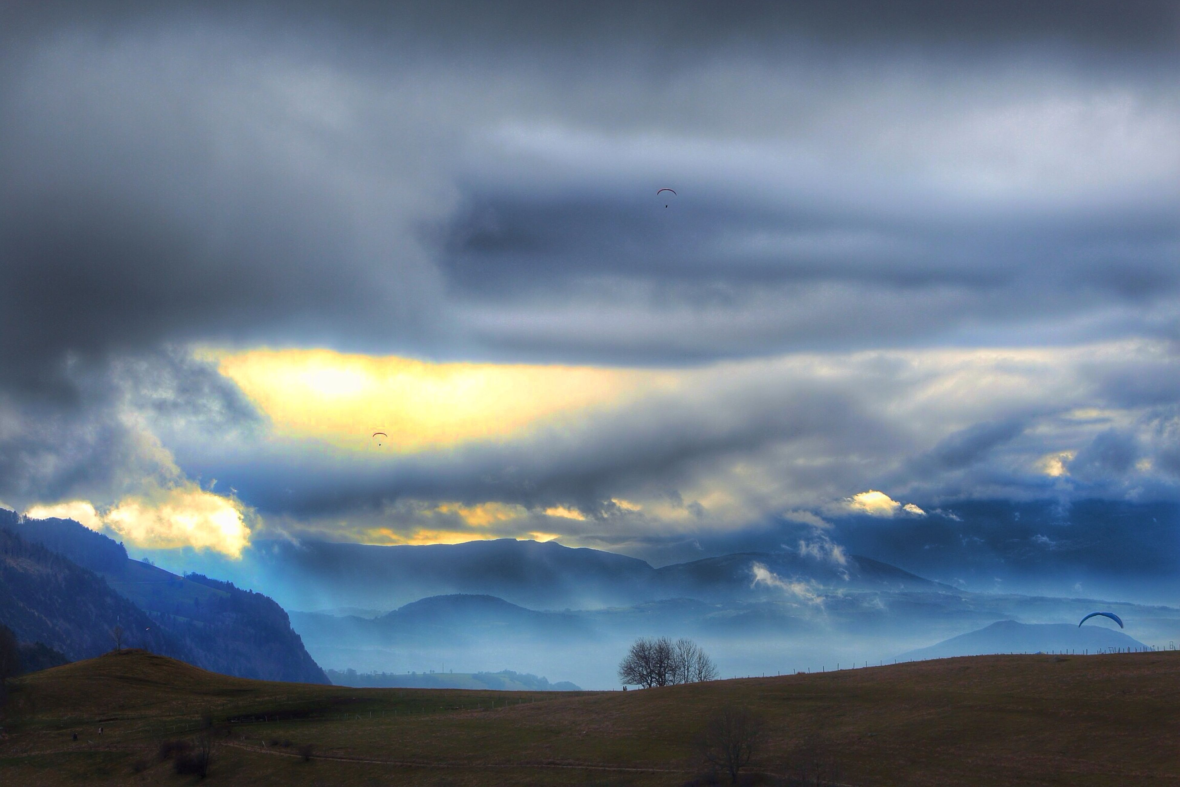 sky, cloud - sky, tranquil scene, scenics, tranquility, landscape, mountain, beauty in nature, cloudy, nature, sunset, cloud, weather, silhouette, idyllic, non-urban scene, mountain range, dusk, overcast, flying