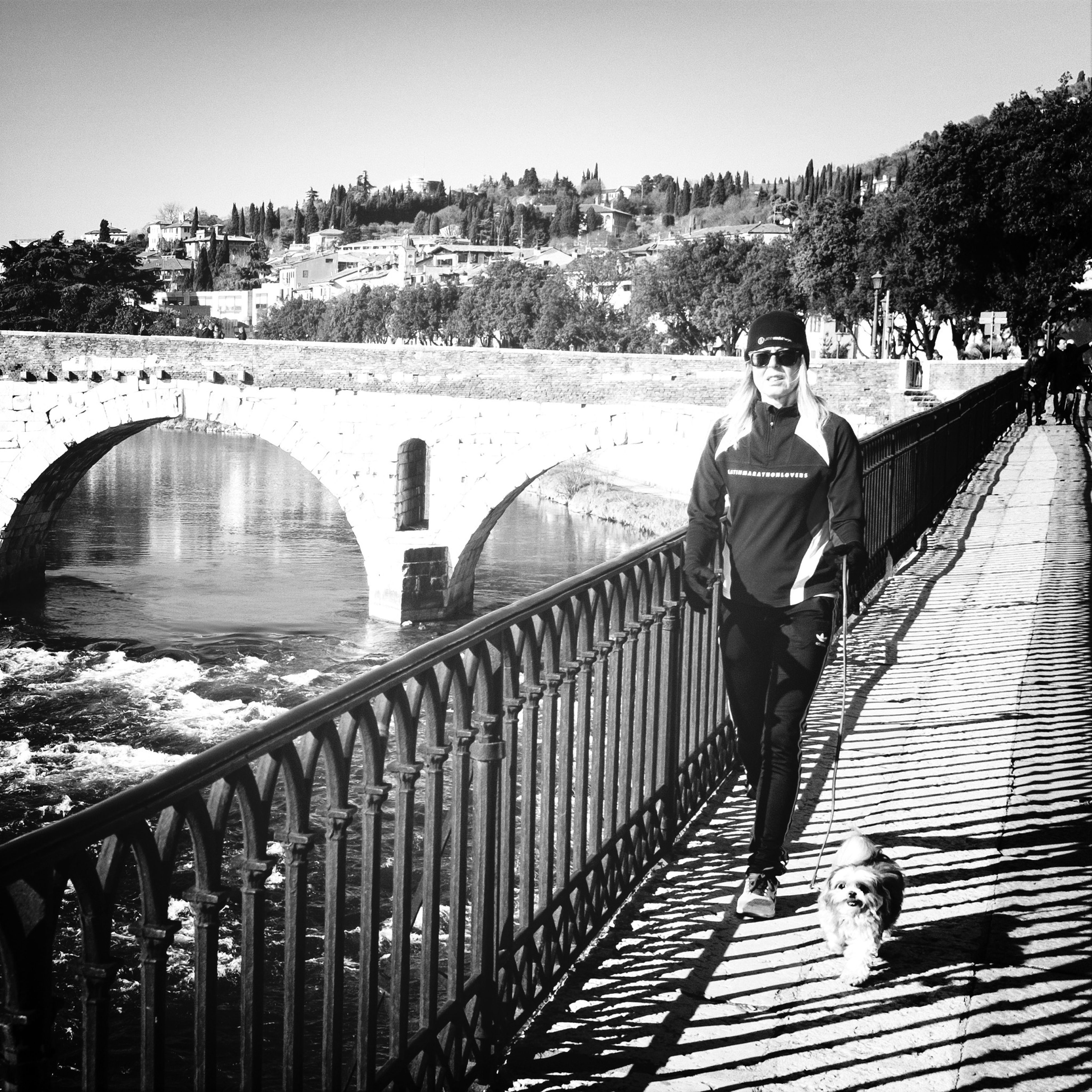 railing, lifestyles, clear sky, built structure, bridge - man made structure, architecture, leisure activity, connection, full length, men, transportation, casual clothing, building exterior, river, water, walking, standing, rear view