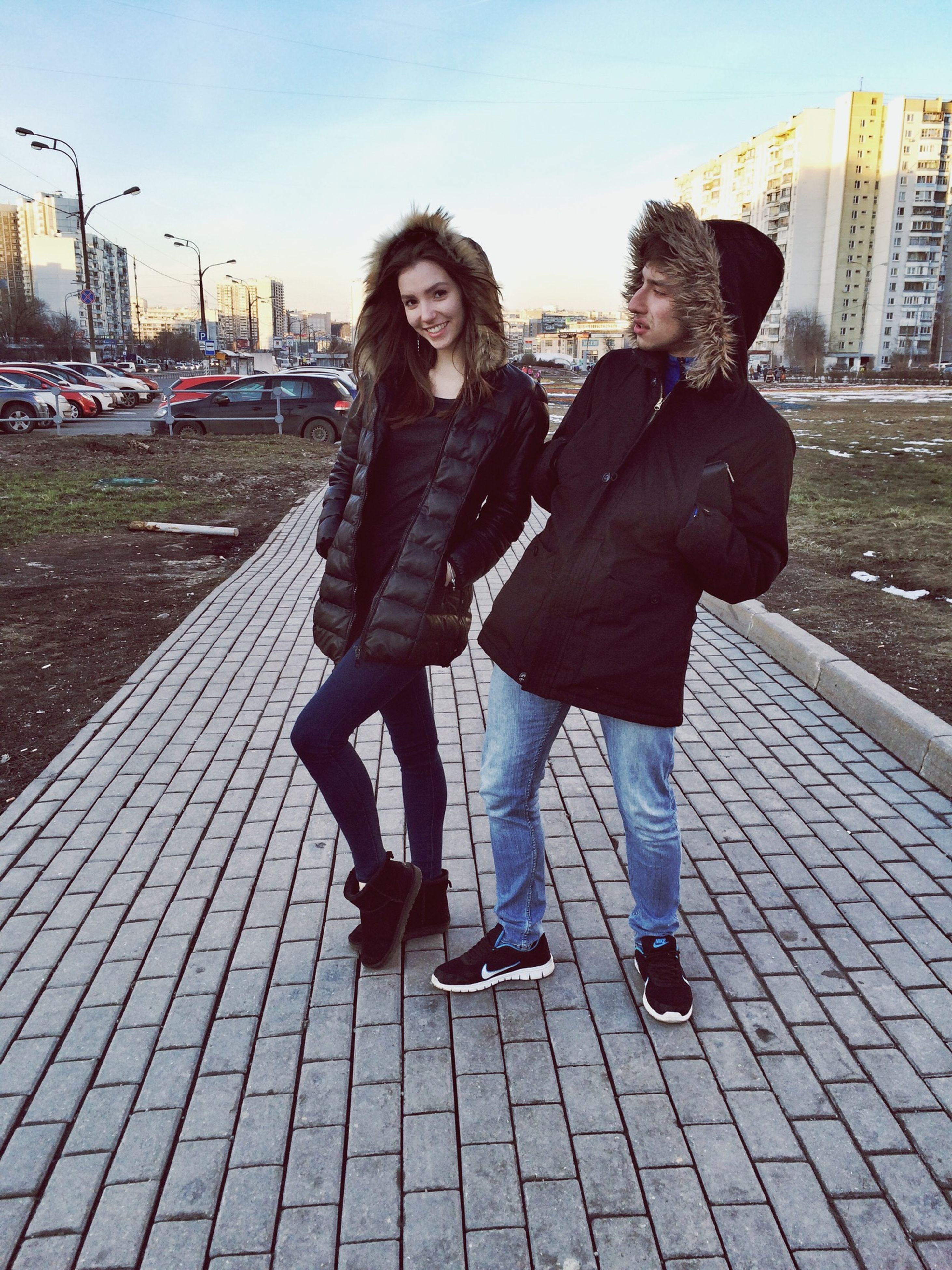 lifestyles, full length, casual clothing, leisure activity, young adult, person, standing, front view, building exterior, young women, city, looking at camera, built structure, portrait, architecture, warm clothing, street