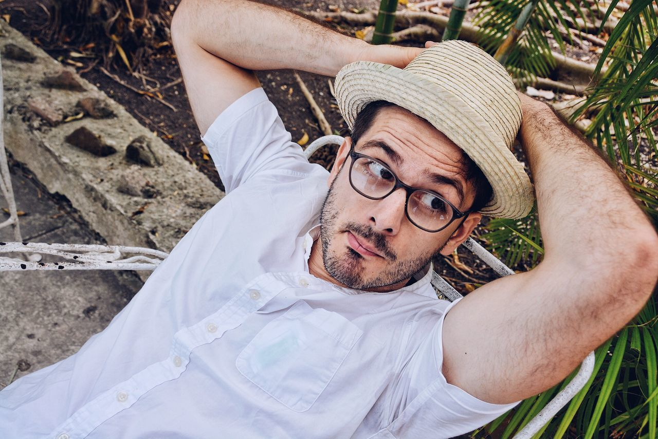 A handsome man. One Person Portrait Adults Only Lying Down Young Adult People Close-up Chilling Real People Relaxing Relaxing Time Relax Resting Break Sitting Down Hat Straw Hat Cuban Hat Dressed In White Glasses The Portraitist - 2017 EyeEm Awards Cuba Havana La Habana