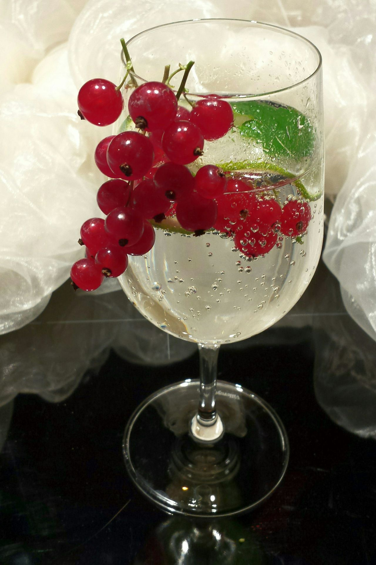 Visual Feast Yummy Drink Appetitlich Wine Glass White Chiffon Black Background Prickelnder Drink Minze Limettenscheibe Cucumber Slices Kohlensäureperlen Sprudel Rote Johannisbeeren Johannisbeeren Red Berries Drink No People Close Up Close-up Freshness Sprudelwasser Sprudelndes Wasser