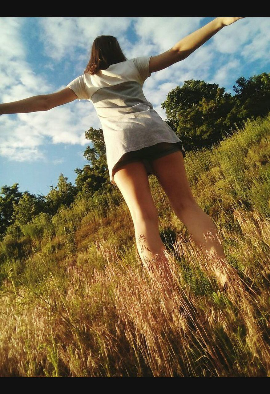 tree, real people, full length, grass, one person, casual clothing, leisure activity, lifestyles, nature, rear view, outdoors, growth, day, field, sky, young women, standing, young adult, women, beauty in nature, people