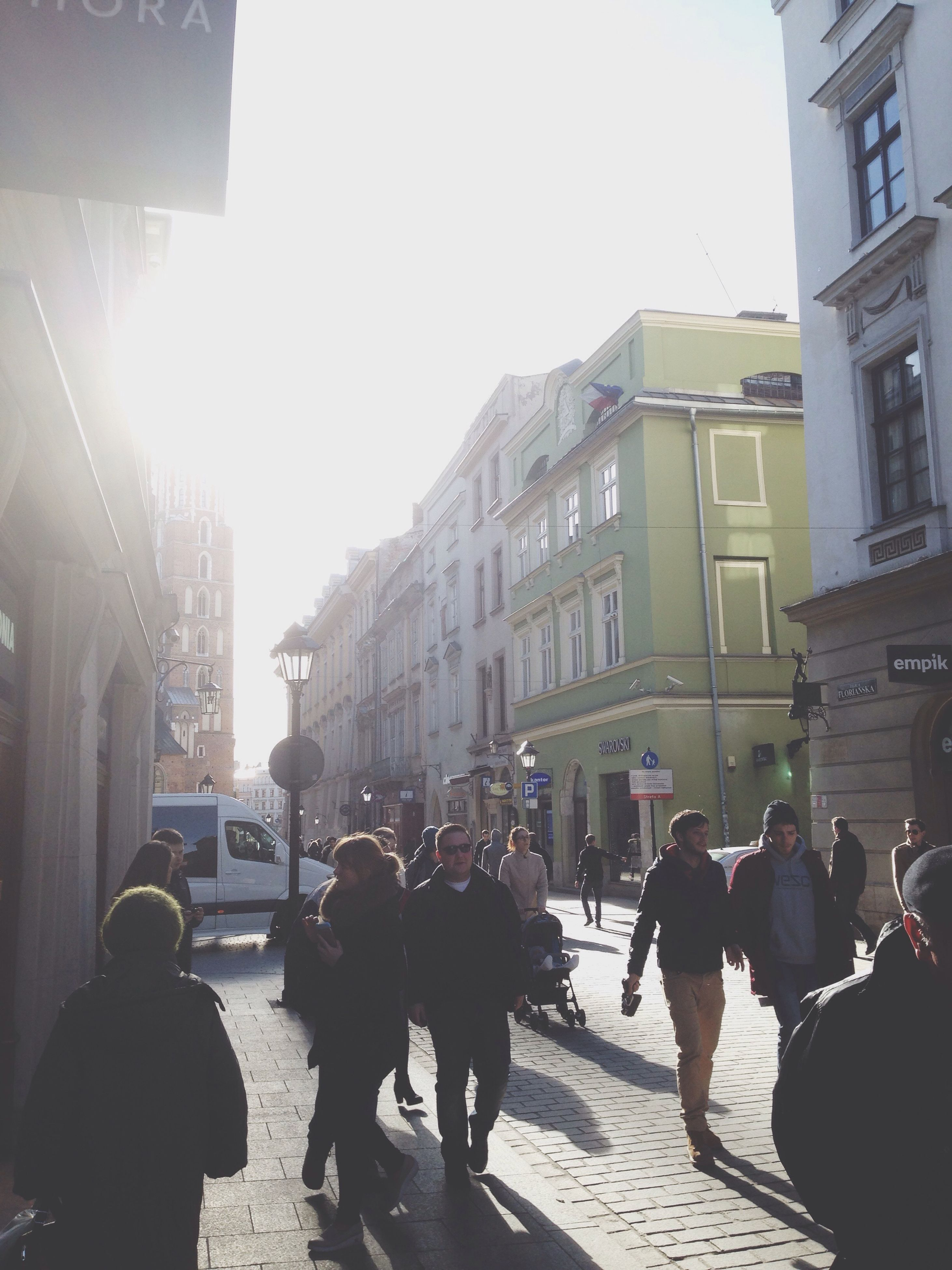 building exterior, architecture, built structure, large group of people, street, men, clear sky, lifestyles, city, walking, person, city life, city street, car, leisure activity, transportation, sunlight, medium group of people, road