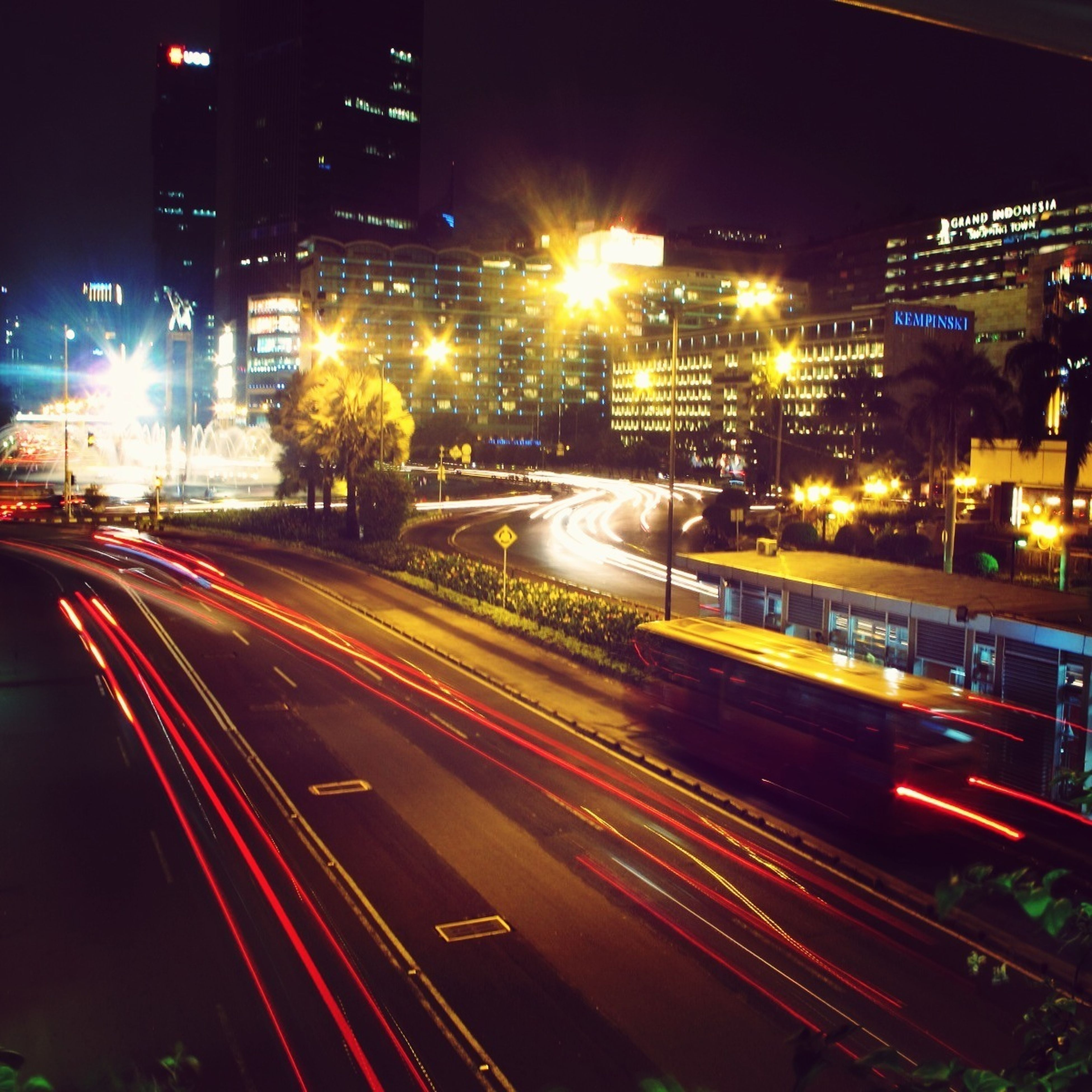 illuminated, night, long exposure, light trail, city, building exterior, motion, architecture, speed, transportation, built structure, street, traffic, city life, road, blurred motion, city street, street light, high angle view, car