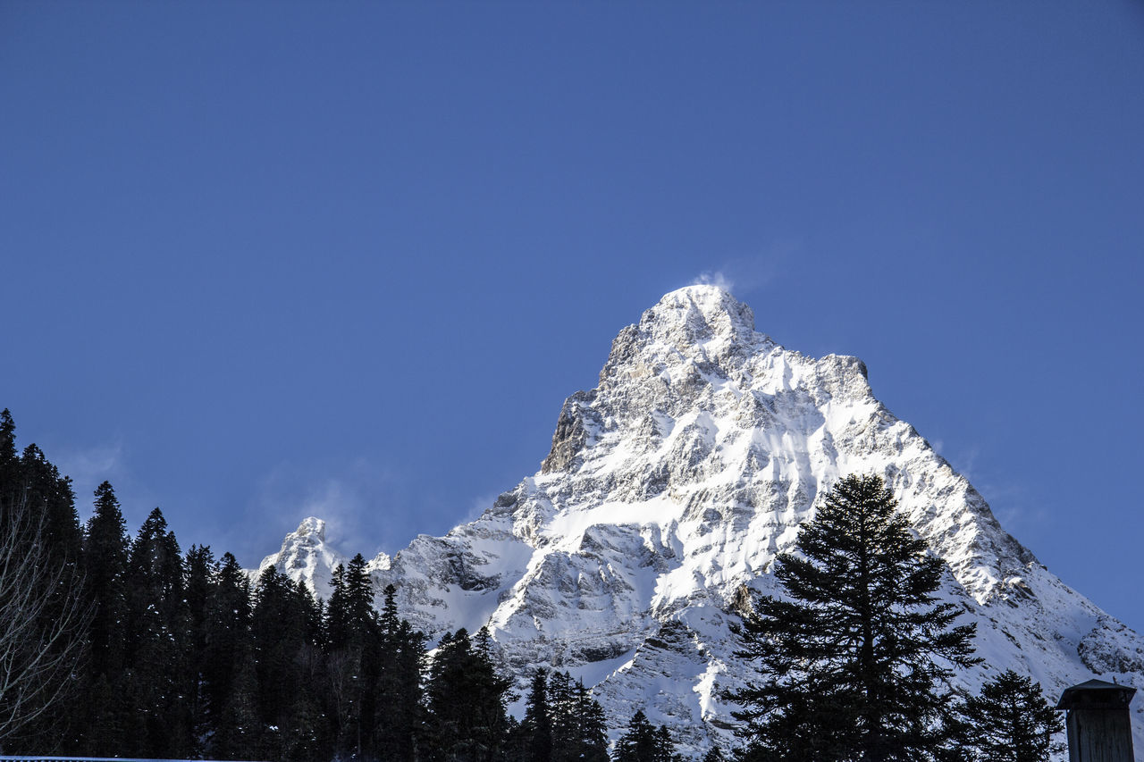 snow, winter, mountain, cold temperature, nature, beauty in nature, scenics, tranquility, copy space, tree, tranquil scene, no people, outdoors, clear sky, snowcapped mountain, landscape, day, blue, forest, mountain range, sky, range