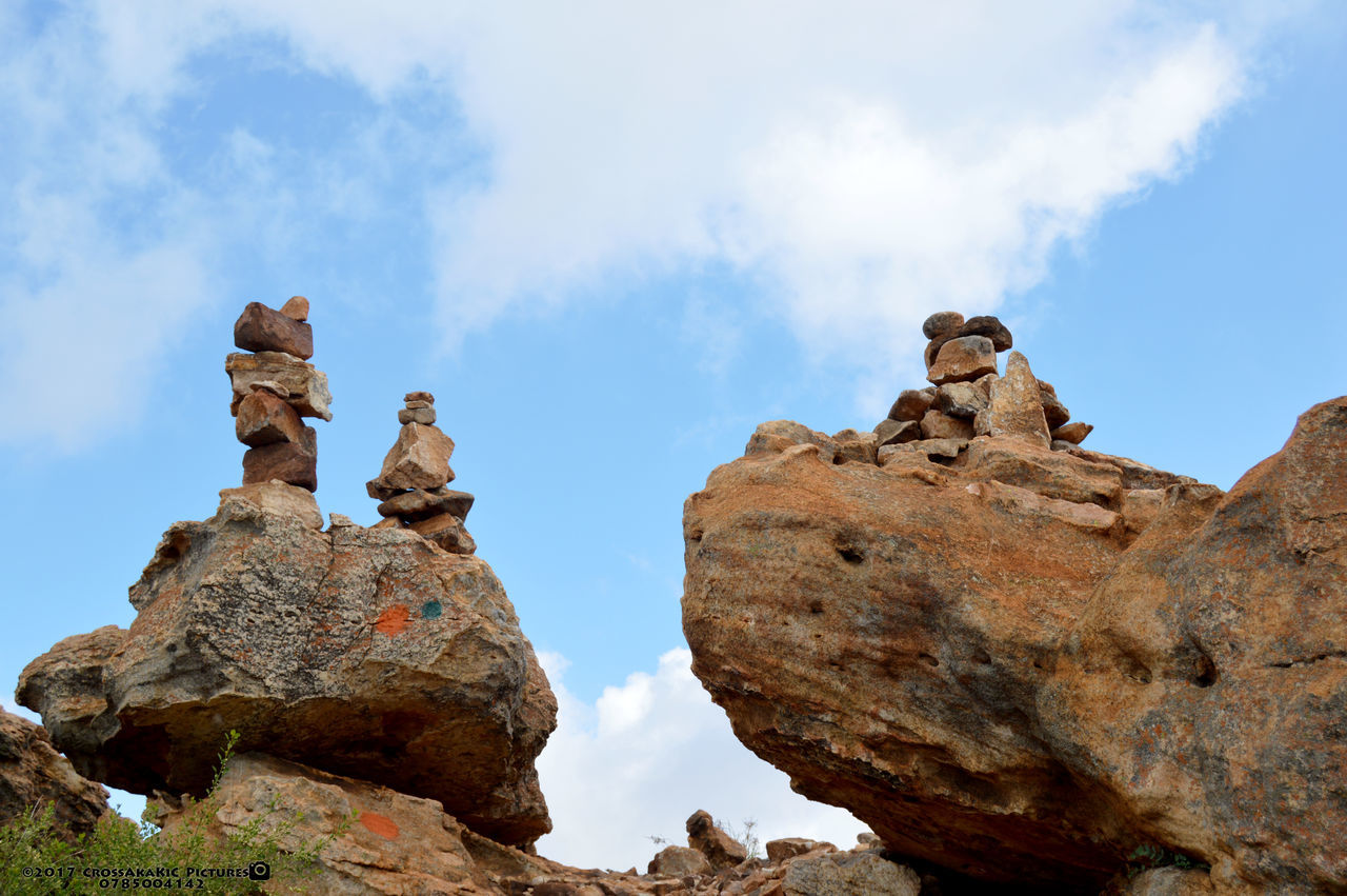 rock - object, cloud - sky, sky, rock formation, day, low angle view, outdoors, nature, no people, beauty in nature, bird, animal themes, perching