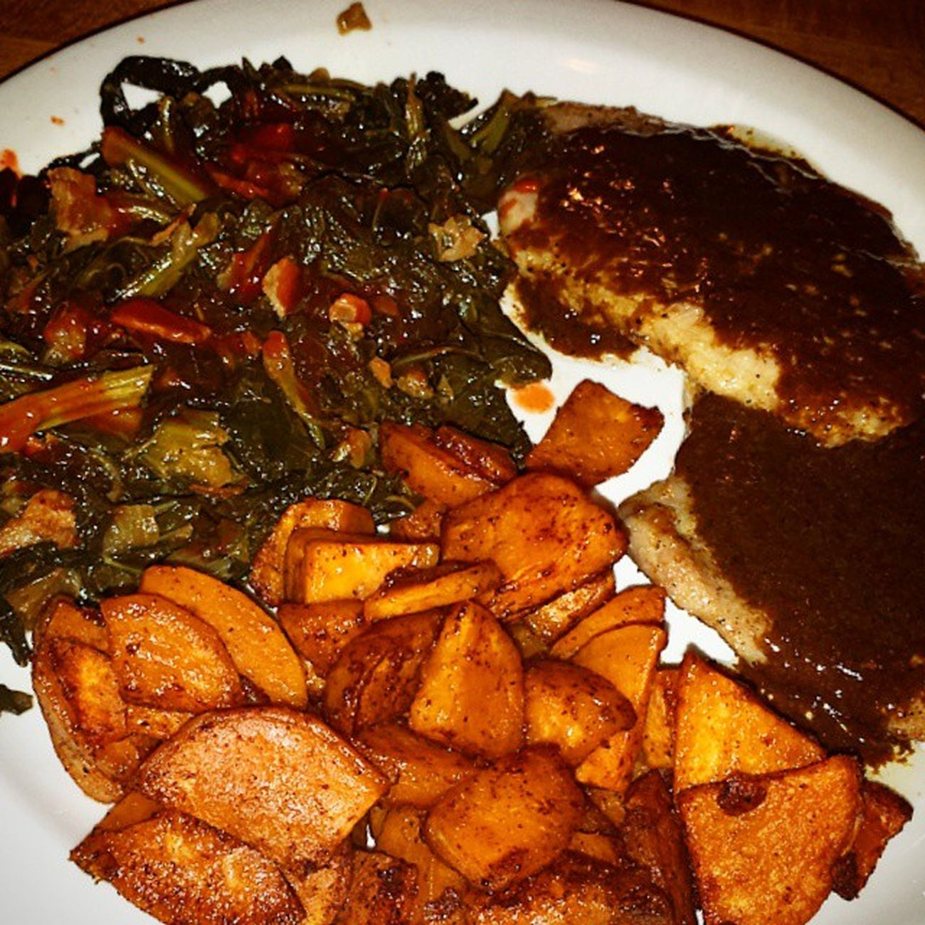 "Full on Paleo meal tonight! Pan ""fried"" pork chops, Paleo gravy (pan drippings, coconut milk, and a tsp tapioca flour), homemade greens trio (collards, kale, and turnip) with onions, bacon and hot sauce, and oven roasted cinnamon sweet potatoes. I put half of this plate up for lunch tomorrow and I'm still STUFFED!!! Paleo Whatsfordinner Porkchops PaleoGravy SweetPotatoes EatClean IAmStuffed"