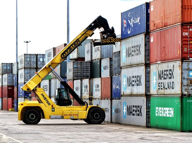 A heavy machine lifter stacking rows of shipping and cargo containers in a freight or goods yard. Shipping Containers Cargo Container Export Import Industry Lifter Stacker Stacking Machinery Heavy Equipment Freight Goods Machine Machines Container Rail Shipping Terminal Logistics Dock Docks Trade