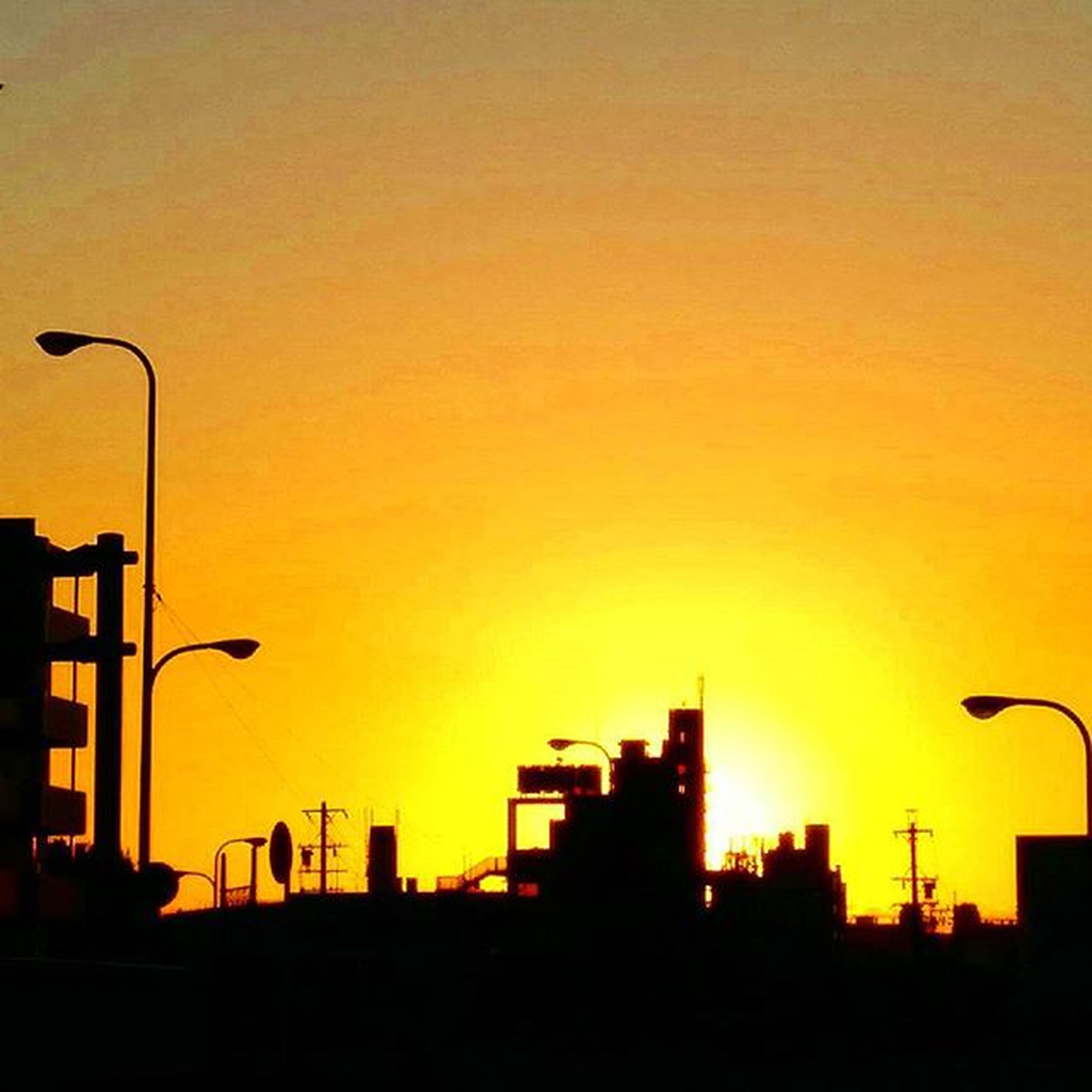 sunset, building exterior, architecture, built structure, silhouette, orange color, city, copy space, clear sky, street light, tower, building, low angle view, sky, sun, skyscraper, outdoors, communications tower, cityscape, tall - high