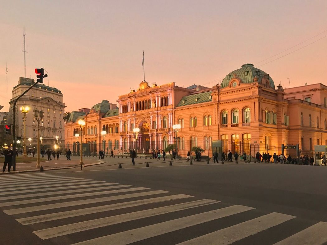 Casa Rosada Presidential Palace Government Building Zebra Crossing Incidental People Sunset French Architecture Neo Baroque Architecture Built Structure Building Exterior City Outdoors Sky Clear Sky Large Group Of People Day People