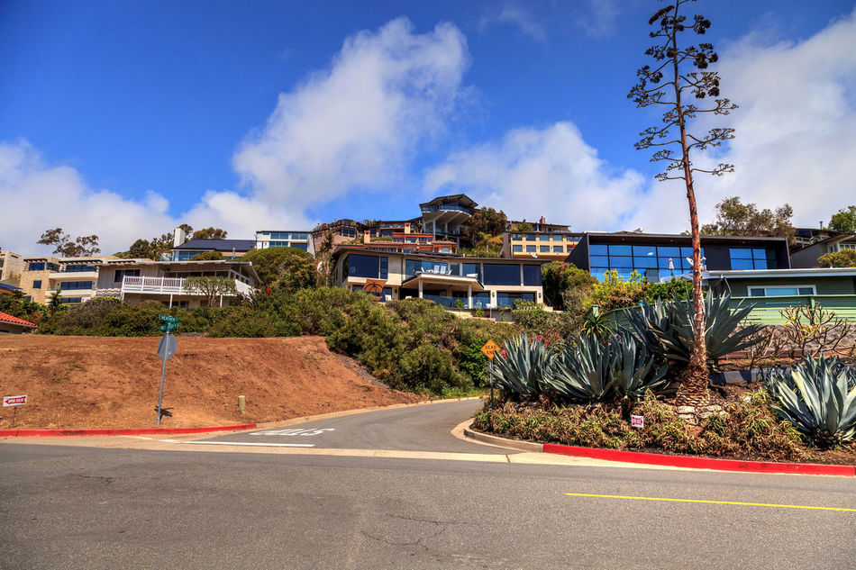 Blue sky above Hillcrest Drive roadside in Laguna Beach, California, USA Adventure Architecture Blue Sky Building Exterior Built Structure California Day Hillcrest Drive Hillside Journey Laguna Beach, CA Mountain No People Orange County, Ca Outdoors Road Road Sky Southern California Town Tree Village