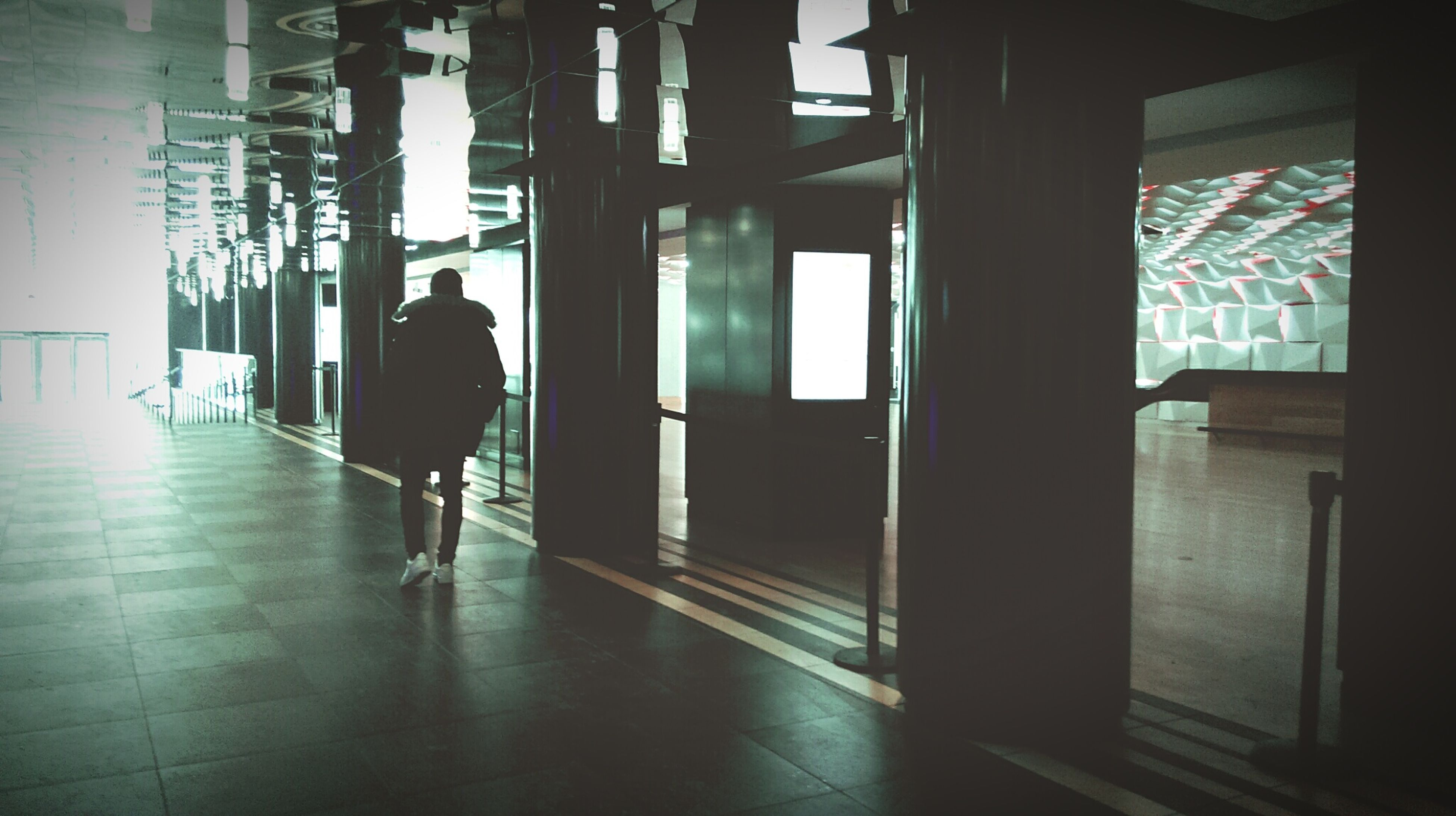 indoors, corridor, architecture, built structure, rear view, walking, men, full length, the way forward, lifestyles, silhouette, window, flooring, person, tiled floor, architectural column, unrecognizable person, sunlight