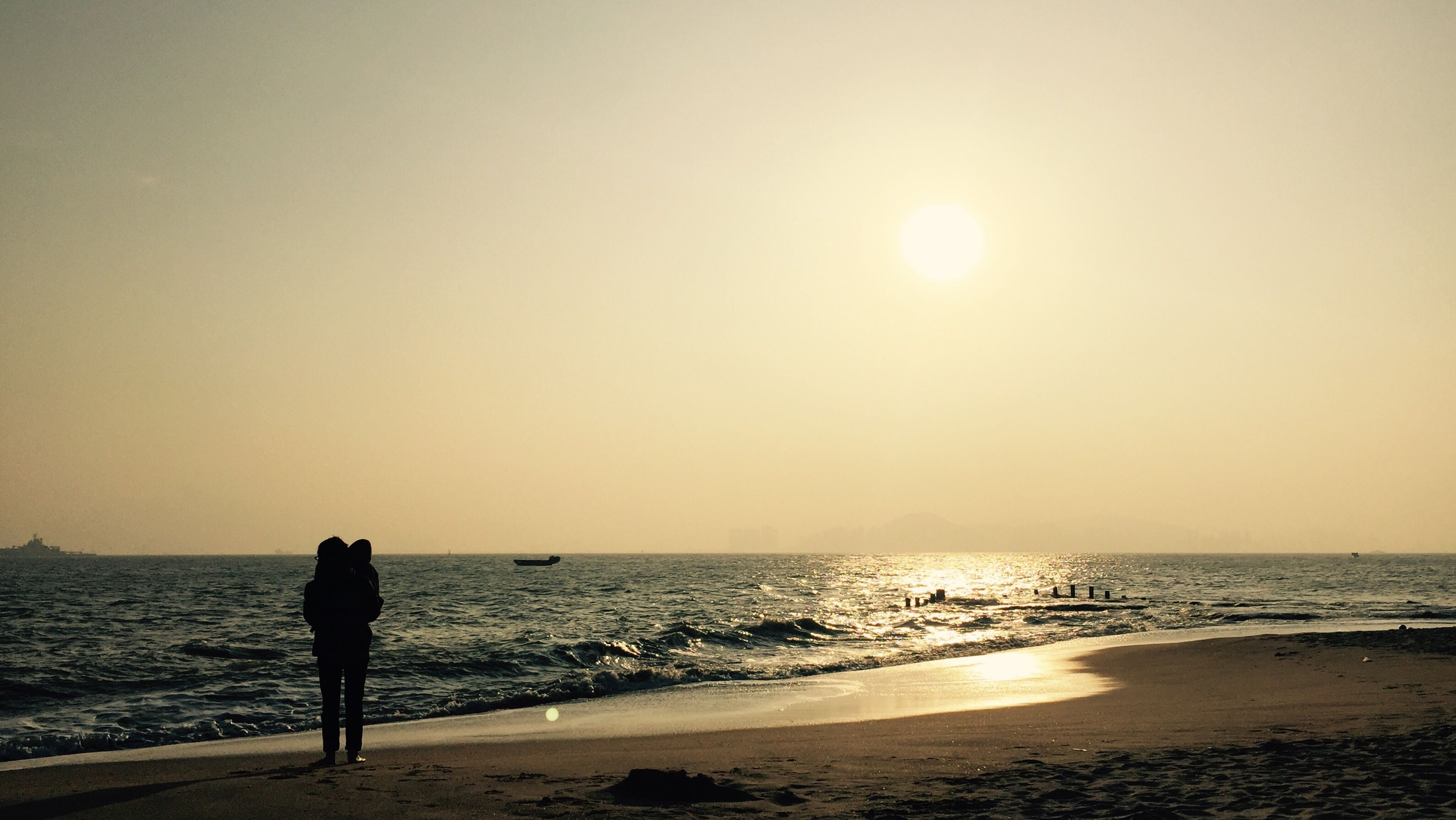 sea, horizon over water, water, sun, beach, sunset, silhouette, scenics, tranquil scene, beauty in nature, shore, tranquility, clear sky, standing, idyllic, nature, copy space, leisure activity