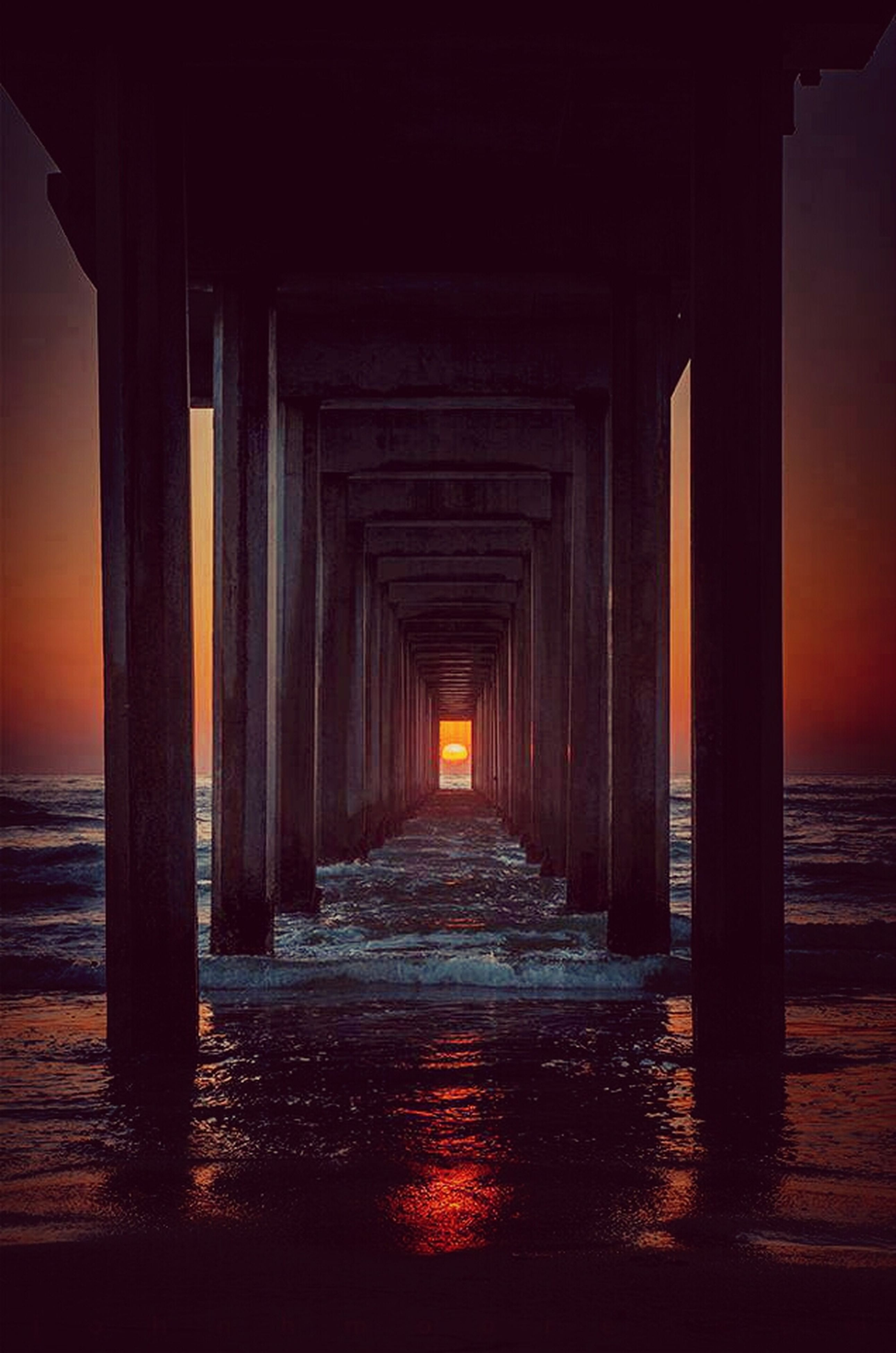 sunset, water, sea, orange color, built structure, architecture, pier, architectural column, the way forward, waterfront, column, reflection, sky, diminishing perspective, in a row, beach, horizon over water, tranquility, nature, scenics
