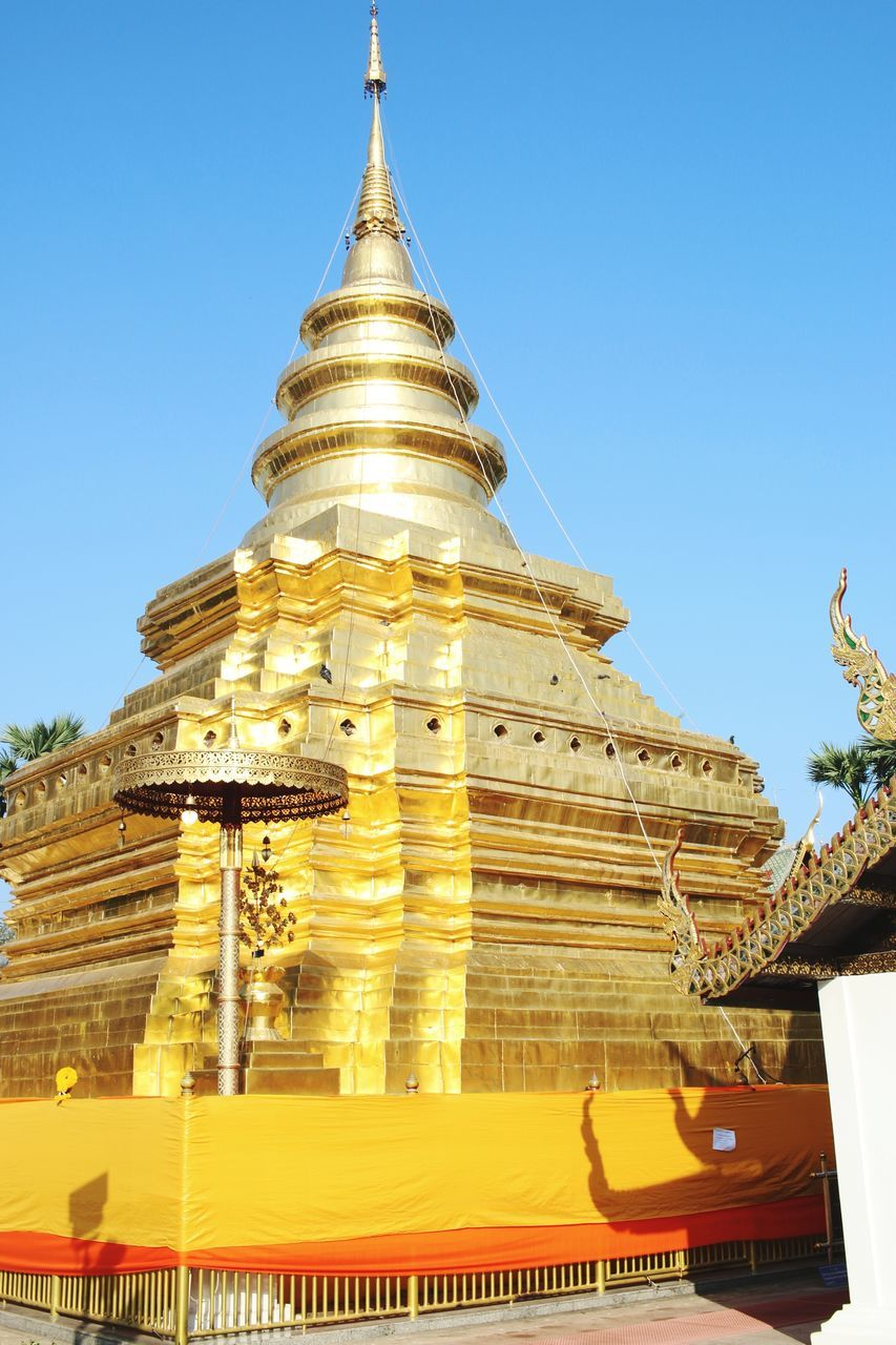 religion, spirituality, place of worship, architecture, pagoda, built structure, building exterior, gold colored, clear sky, low angle view, ancient, outdoors, travel destinations, no people, shrine, history, day, sky, ancient civilization