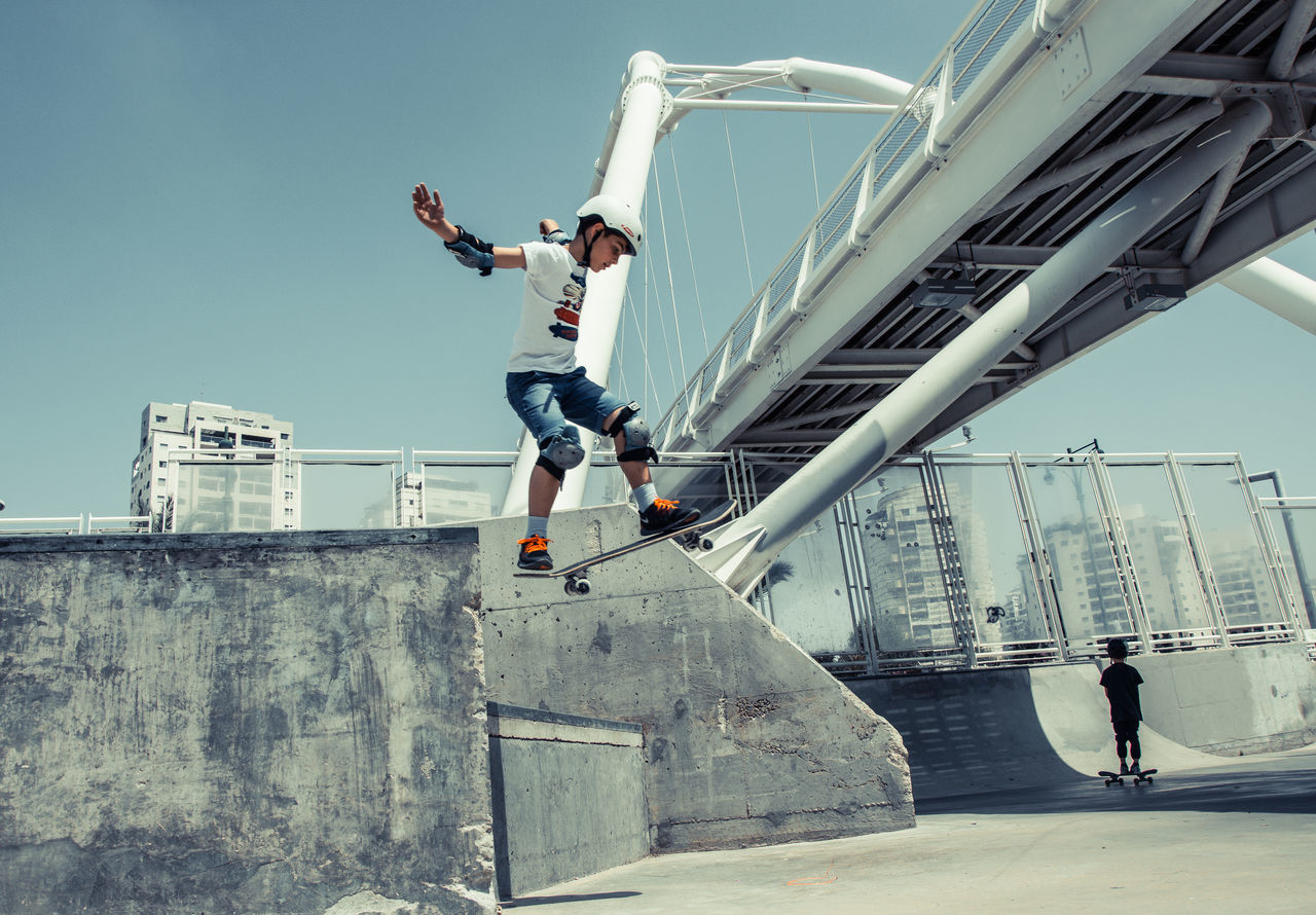 real people, full length, lifestyles, leisure activity, one person, architecture, day, casual clothing, built structure, skill, balance, young adult, outdoors, young men, sunlight, men, low angle view, skateboard park, building exterior, clear sky, sky, stunt, people