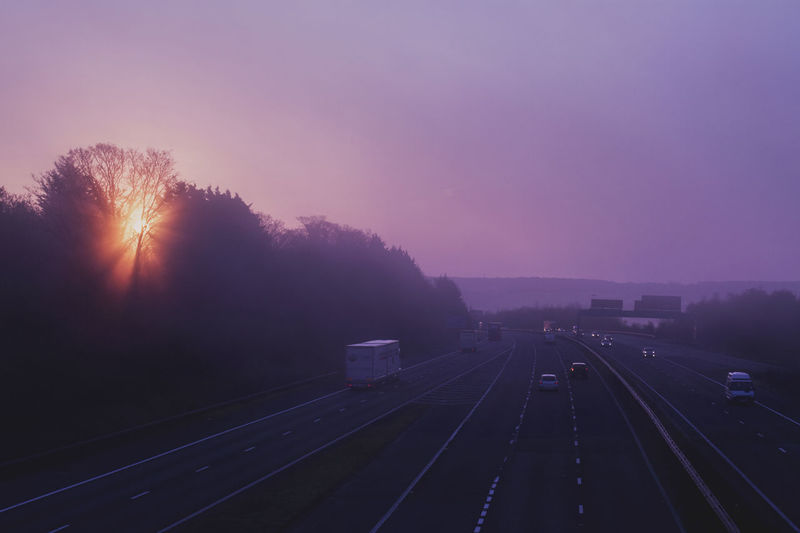 The sun breaks through the silhouetted trees Motorway Motorway Art Motorway View Nature No People Outdoors Silhouette Sky Sunrise Transportation