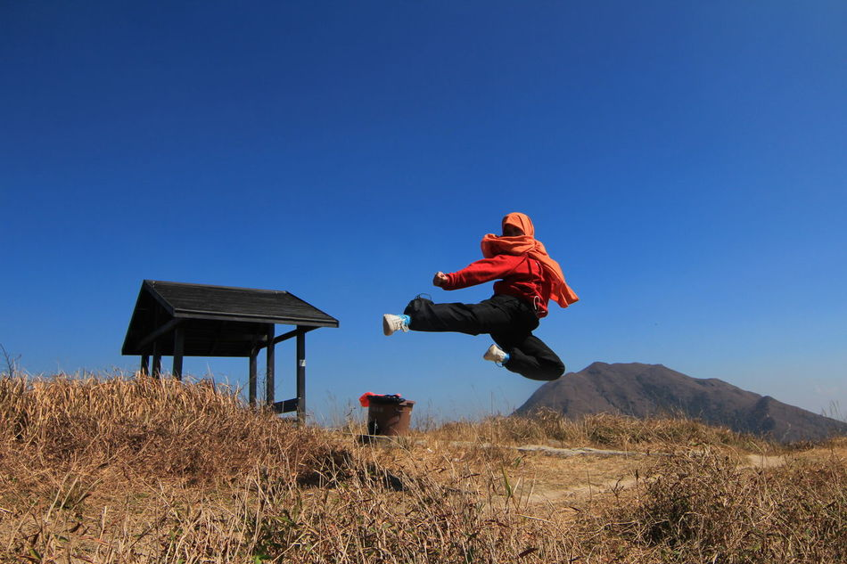 Asti Maria, an Indonesian domestic worker, does an air kick on top of a mountain in Hong Kong. Adult Adults Only Blue Casual Clothing Clear Sky Day Fighter Full Length Heroine Hijab Kungfu  Leisure Activity Low Angle View Mountain Nature Outdoors People Sitting Sky Sunlight Woman