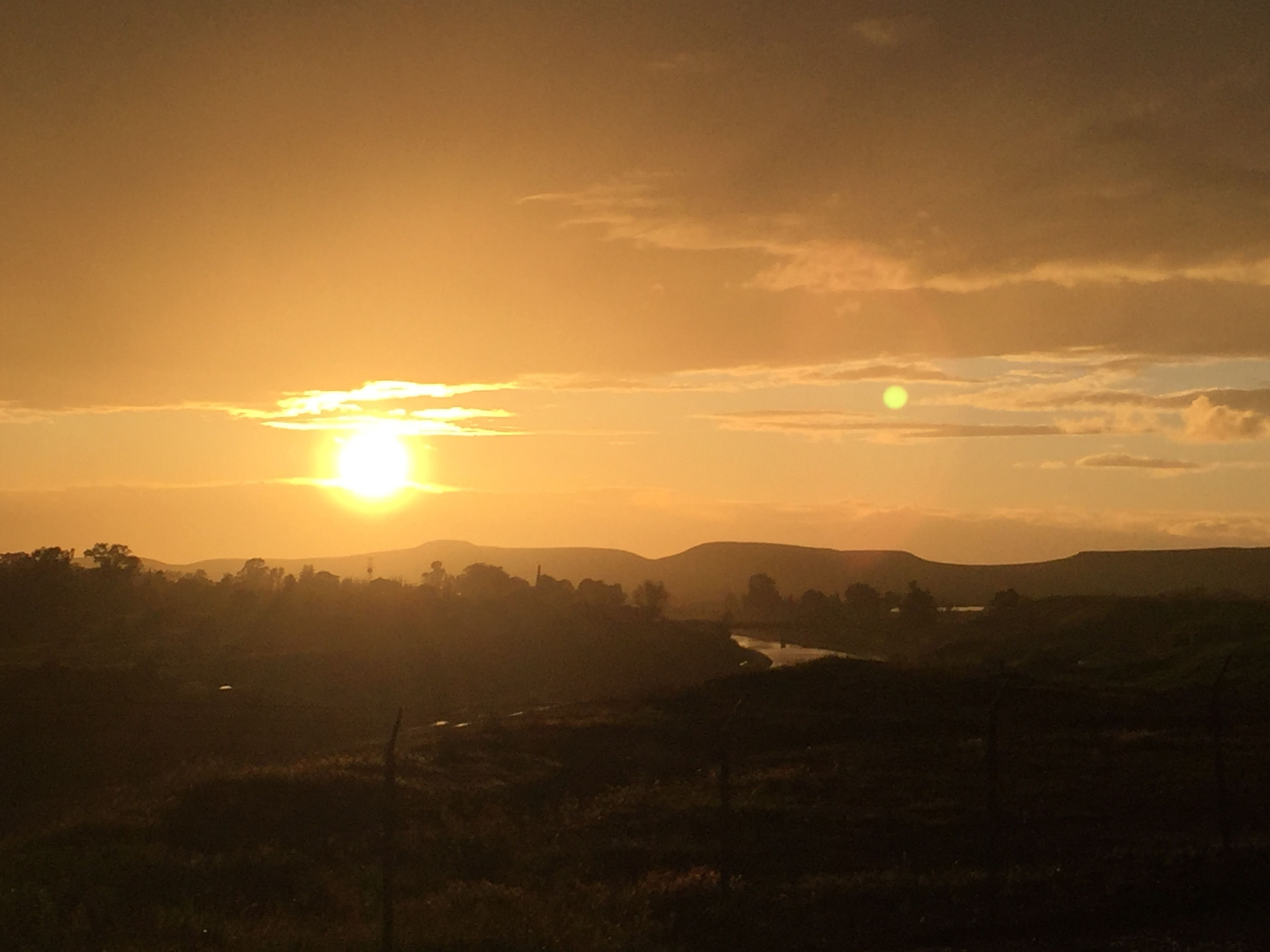 sunset, sun, tranquil scene, scenics, tranquility, sky, beauty in nature, silhouette, landscape, sunbeam, sunlight, nature, mountain, idyllic, orange color, cloud - sky, lens flare, field, cloud, mountain range