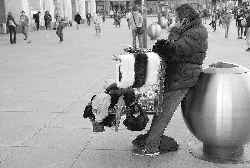 Street vendor with gas masks and other stuff making a call at Berlin Alexanderplatz Authentic Moments Call Candid Day Domestic Animals Gas Masks Large Group Of People Lifestyle Men Outdoors Pets Phone Place Profession Real Life Real People Selling Street Street Photography Women The Street Photographer - 2017 EyeEm Awards Strassenfilm