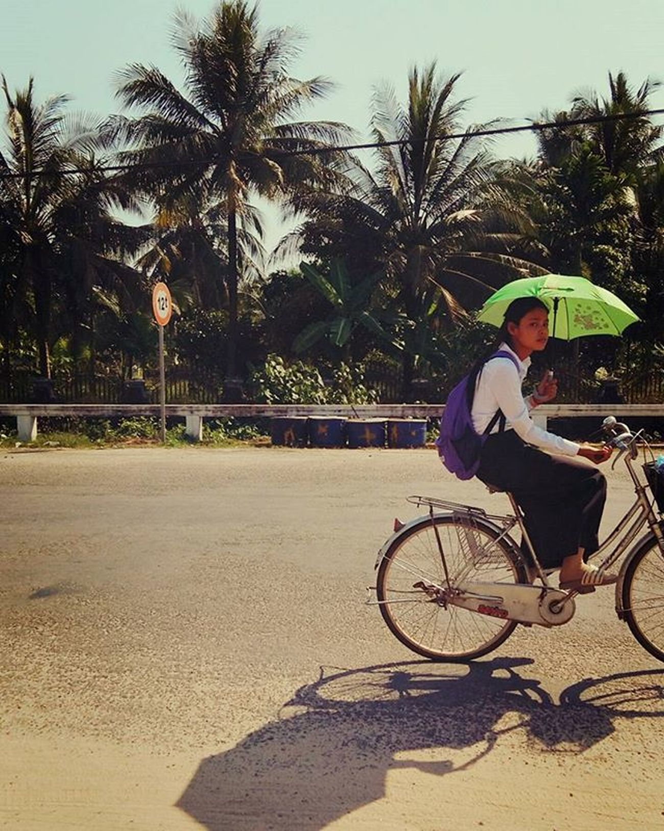 ThrowBackWhenever Buenos días, Sunday! 🌞 Pretty Cambodian Student Pedalling home for lunch after morning school 🚲 🌴 🌴 都話本地人怕曬 穿長袖兼擔遮 Bicycle Umbrella Sunny Sunshine Trees Shadow Kohkong