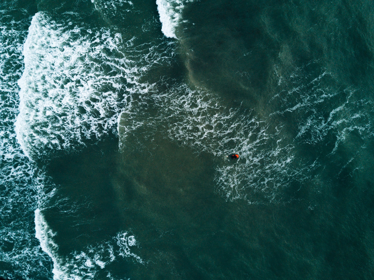 Aerial image of beach and water with waves and surfer Beauty In Nature Day High Angle View Motion Nature One Person Outdoors People Real People Sea Swimming Wake - Water Water Waterfront Wave