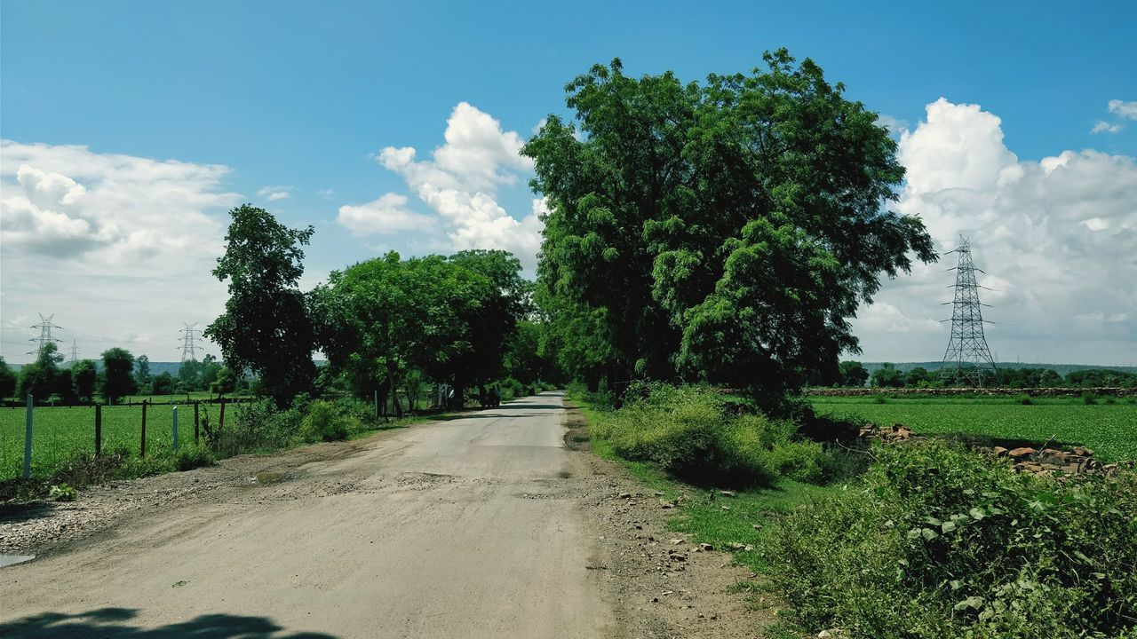Road Amidst Agricultural Field Against Sky