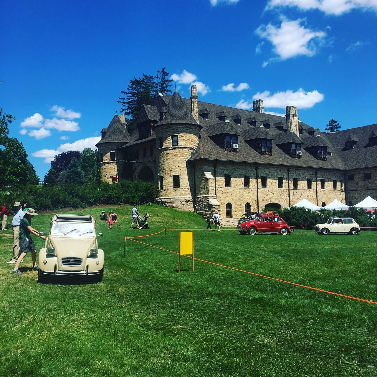 car, grass, architecture, land vehicle, building exterior, day, built structure, transportation, outdoors, travel, real people, sky, green color, tree, nature, travel destinations, men, people