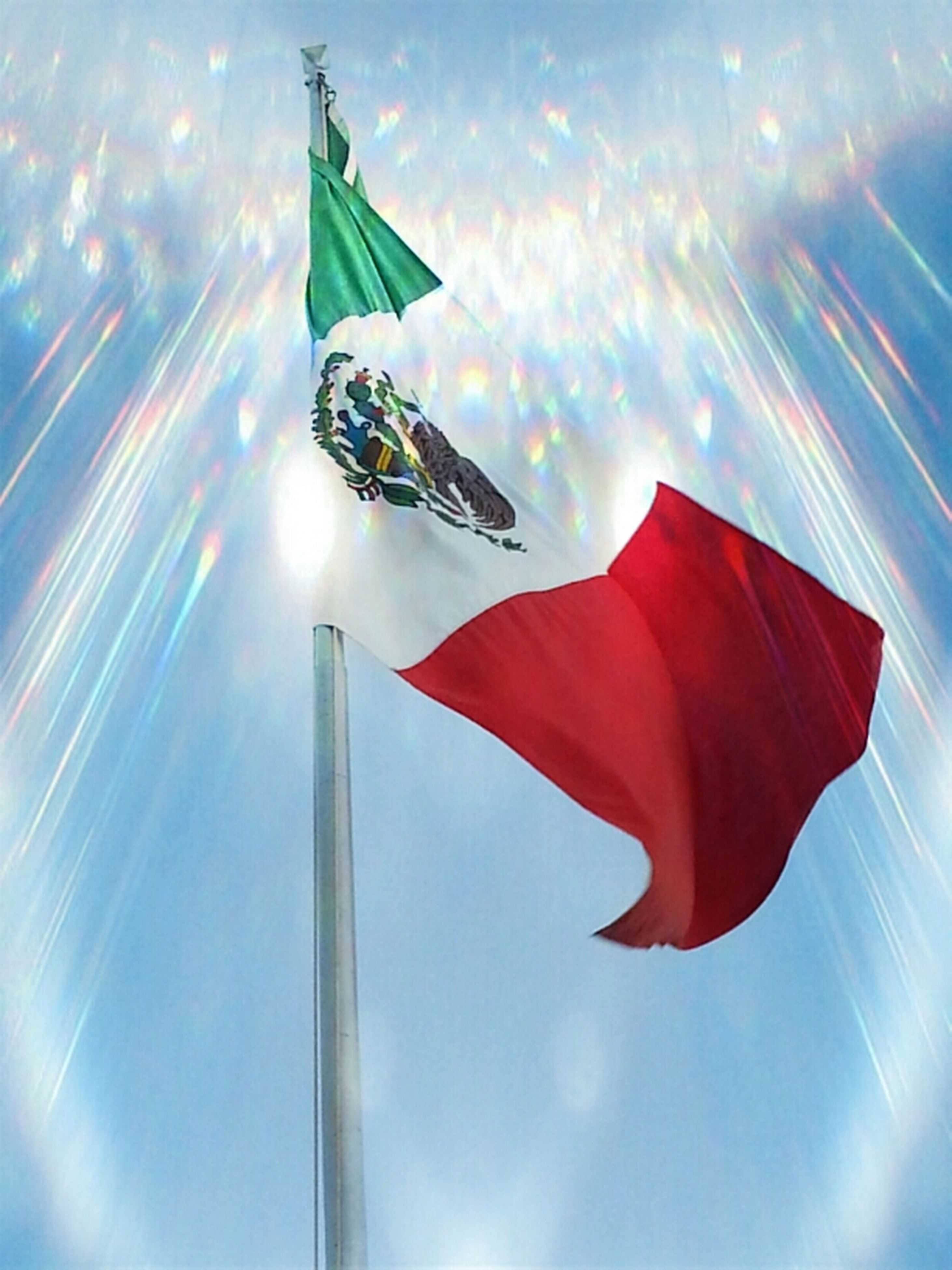 low angle view, flag, sun, sky, sunlight, national flag, sunbeam, patriotism, lens flare, identity, red, wind, multi colored, cloud - sky, day, no people, sunny, outdoors, tall - high, cloud