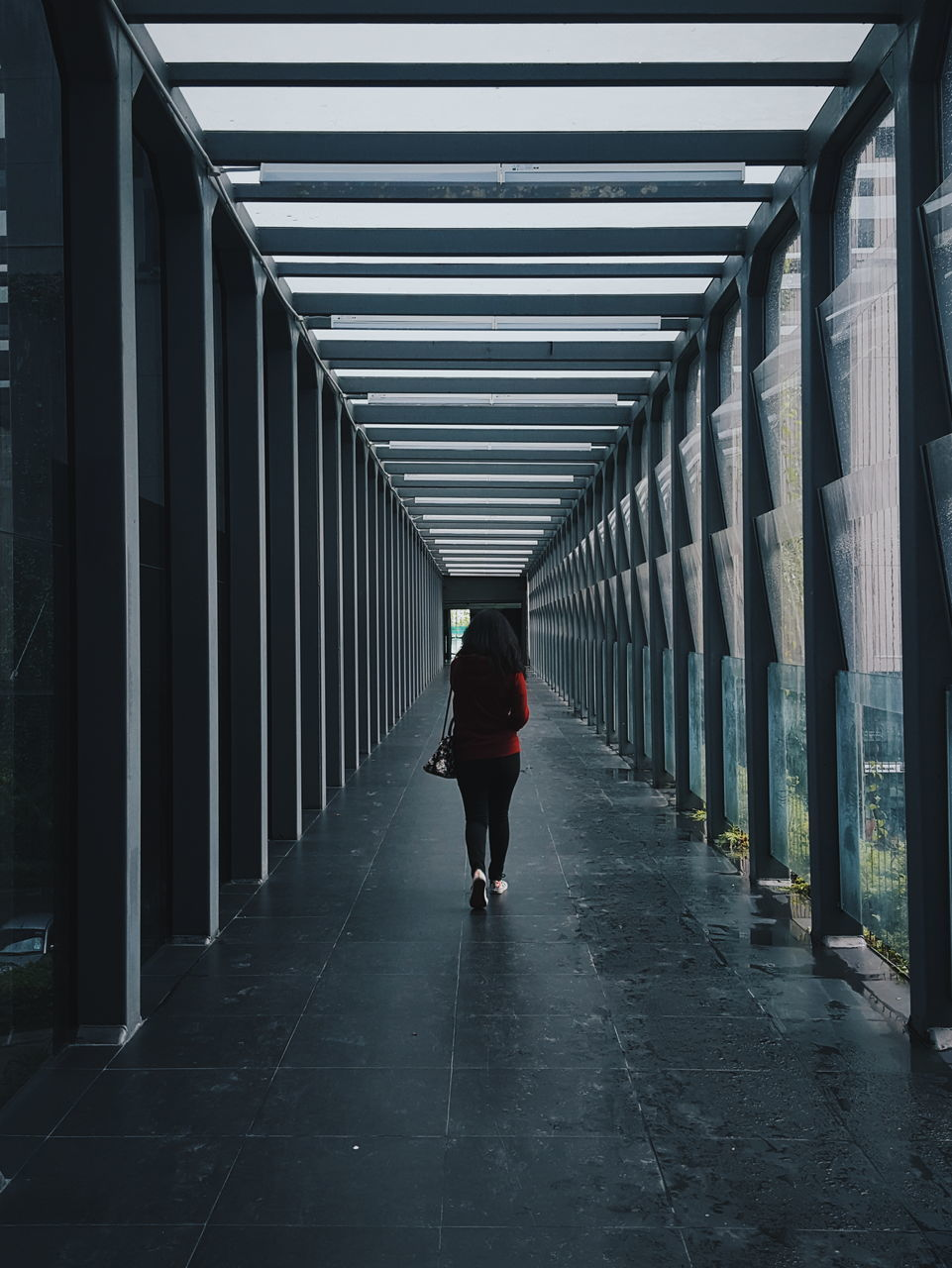 Full Length Rear View Of Woman Walking In Passage